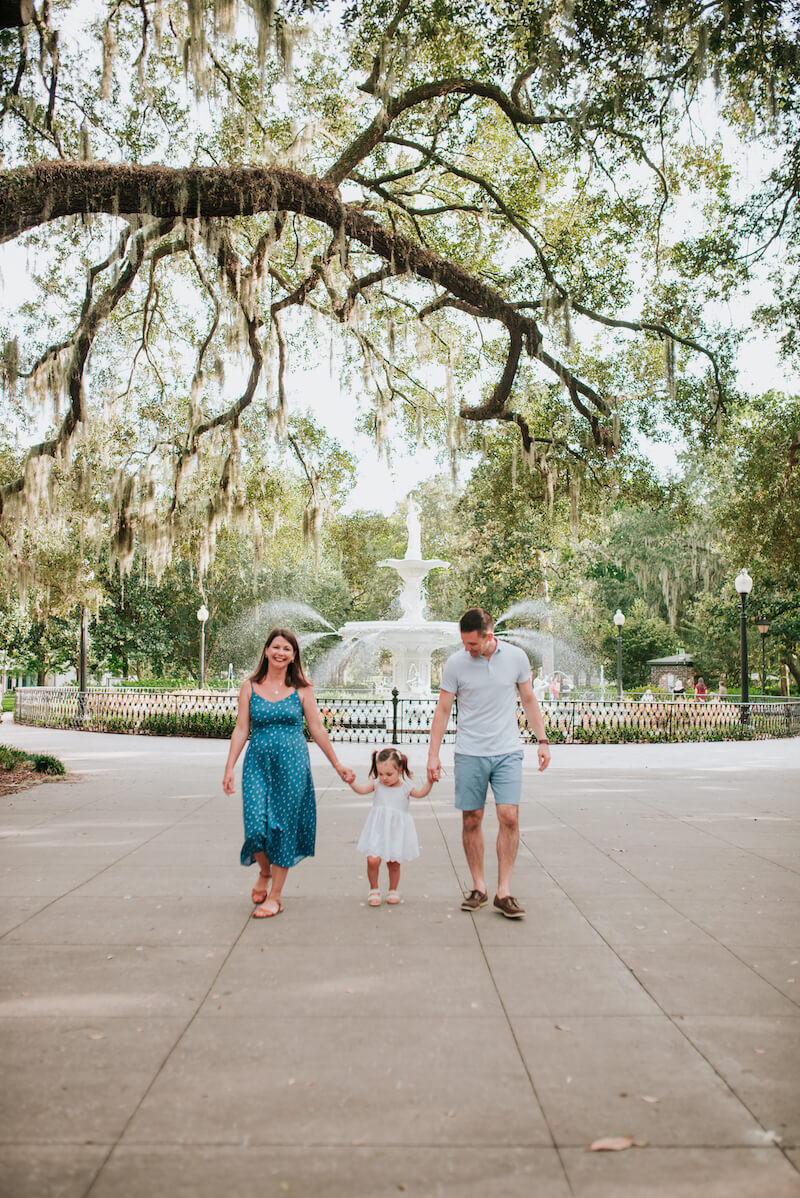 a family of three walking in a park in Savannah, Georgia, United States of America