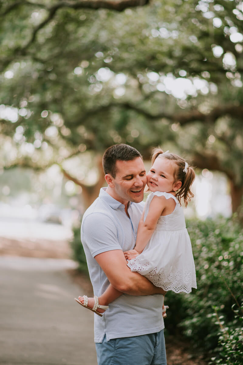 a father holding his daughter in a park in Savannah, Georgia, United States of America