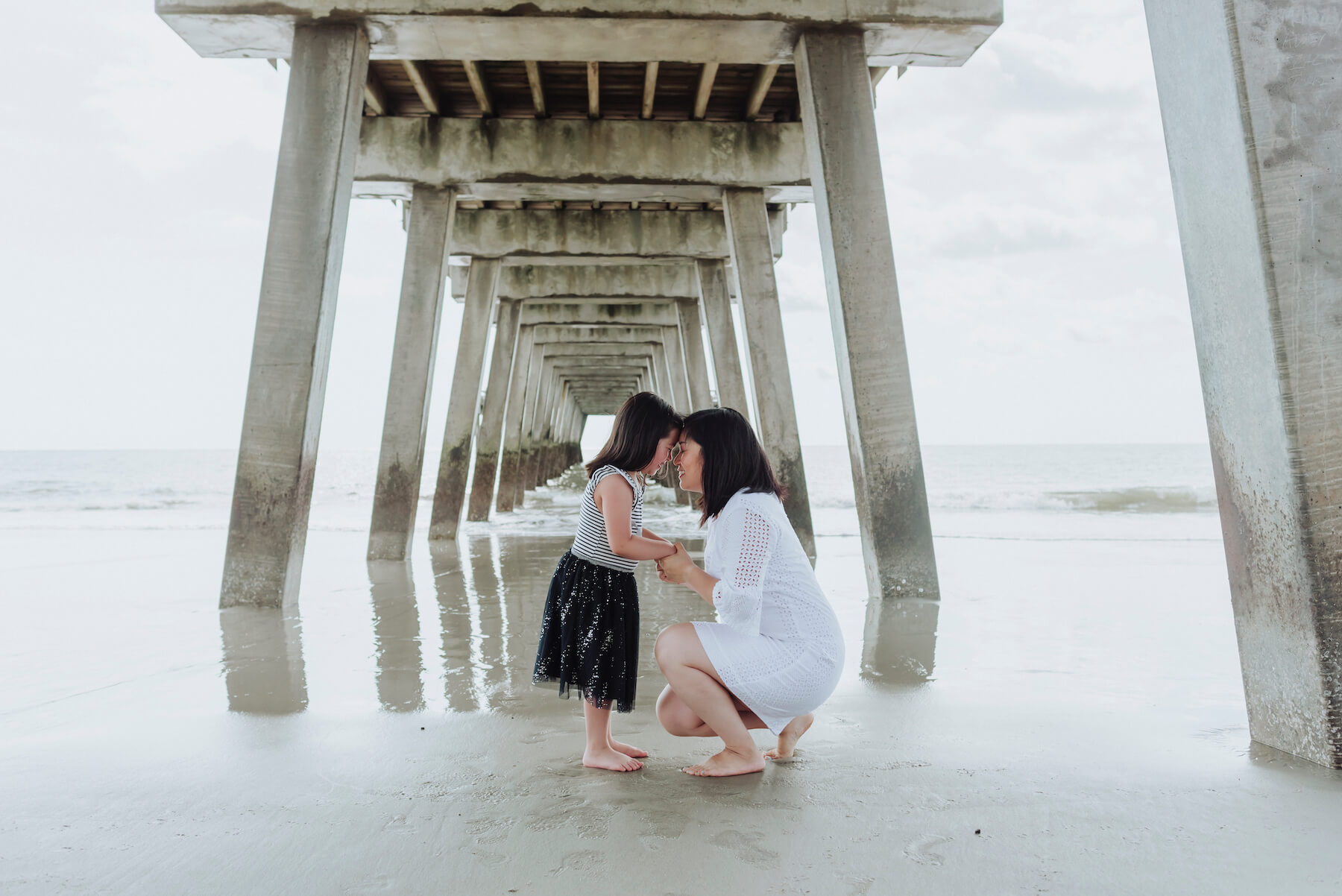 mother and daughter kneeling down under the beach pier in Savannah, Georgia, United States of America