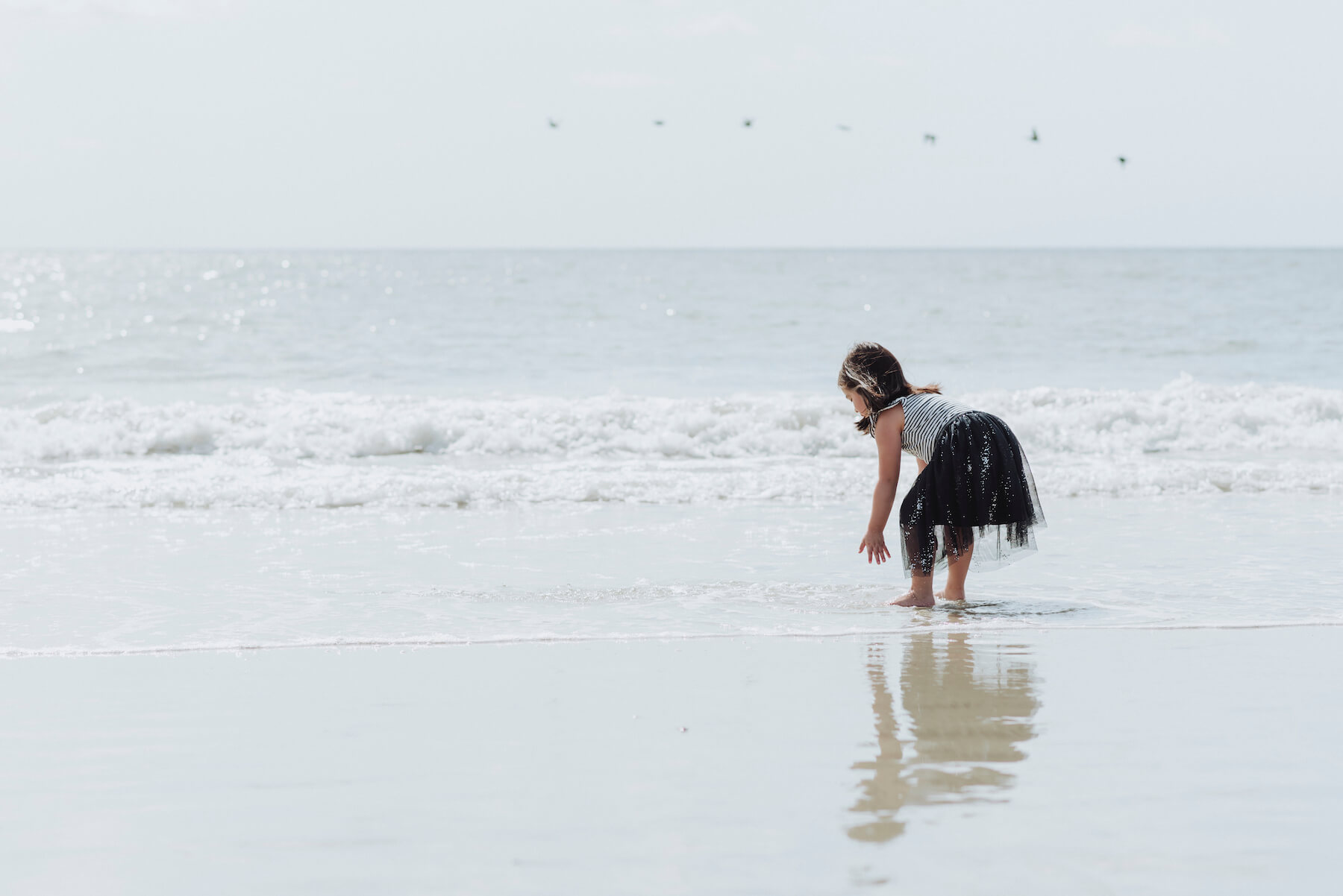 a girl bending over and having fun in the water on a beach in Savannah, Georgia, United States of America