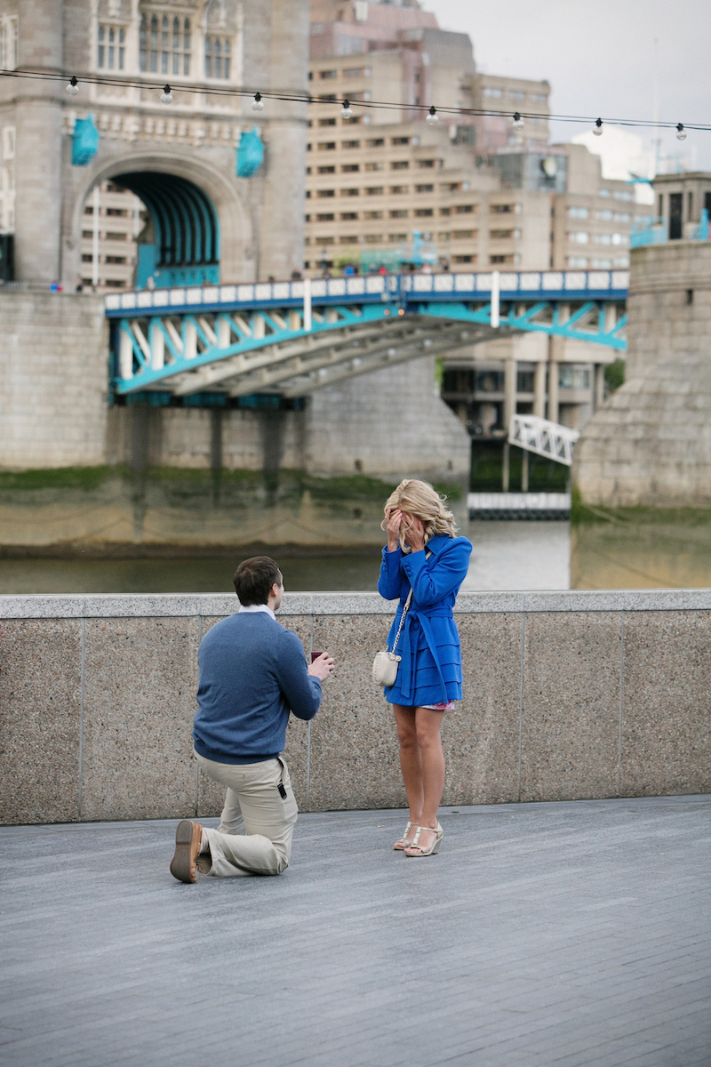 a man is proposing to a woman near the tower bridge in London, England