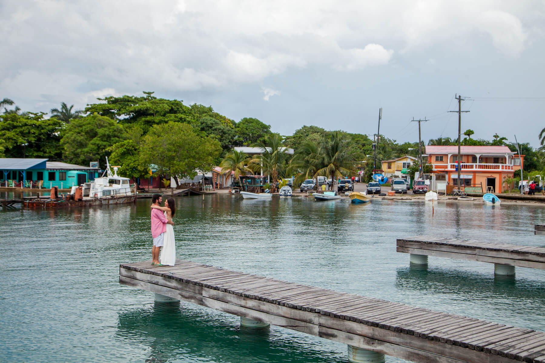 couple holding each other on a dock with the village of Placencia, Belize in the background