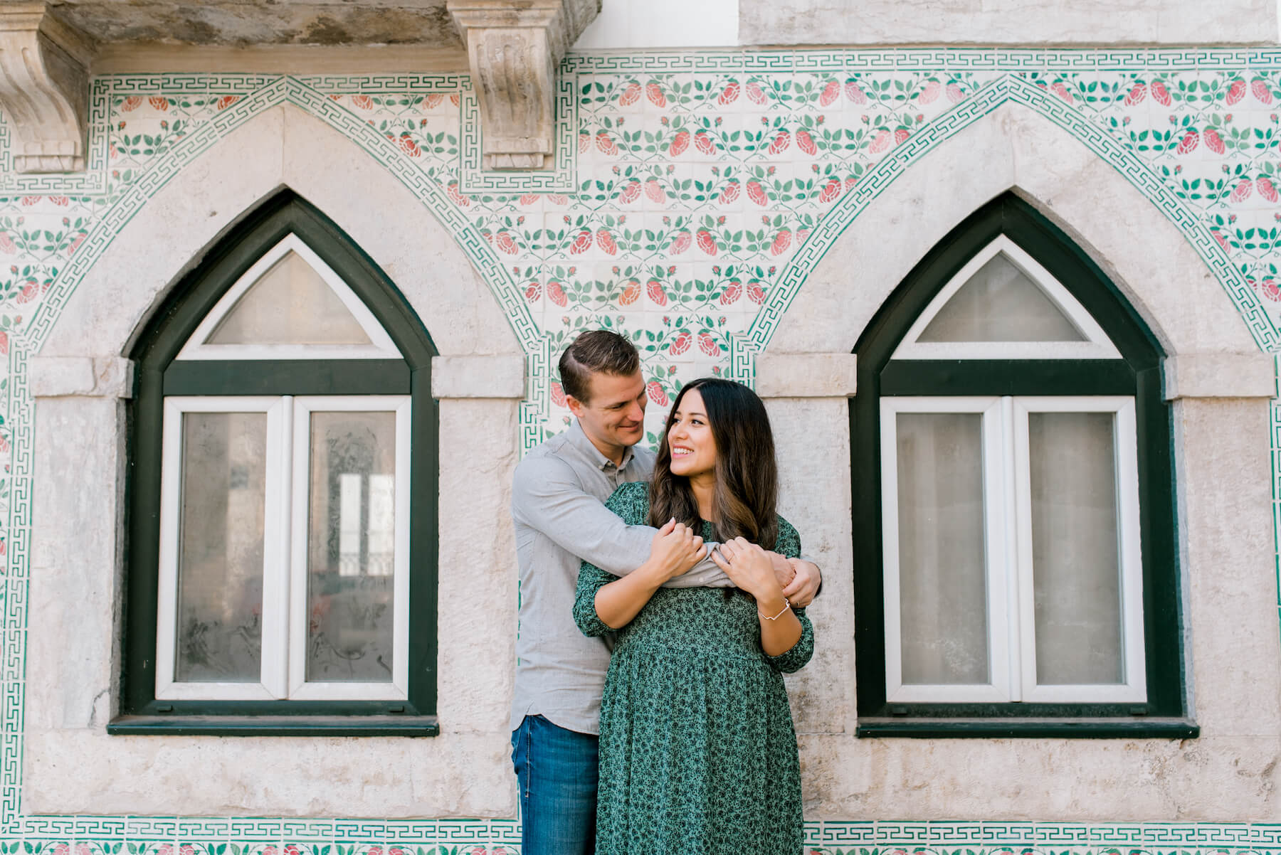 couple hugging each other and standing in front of a colorful building in Lisbon, Portugal