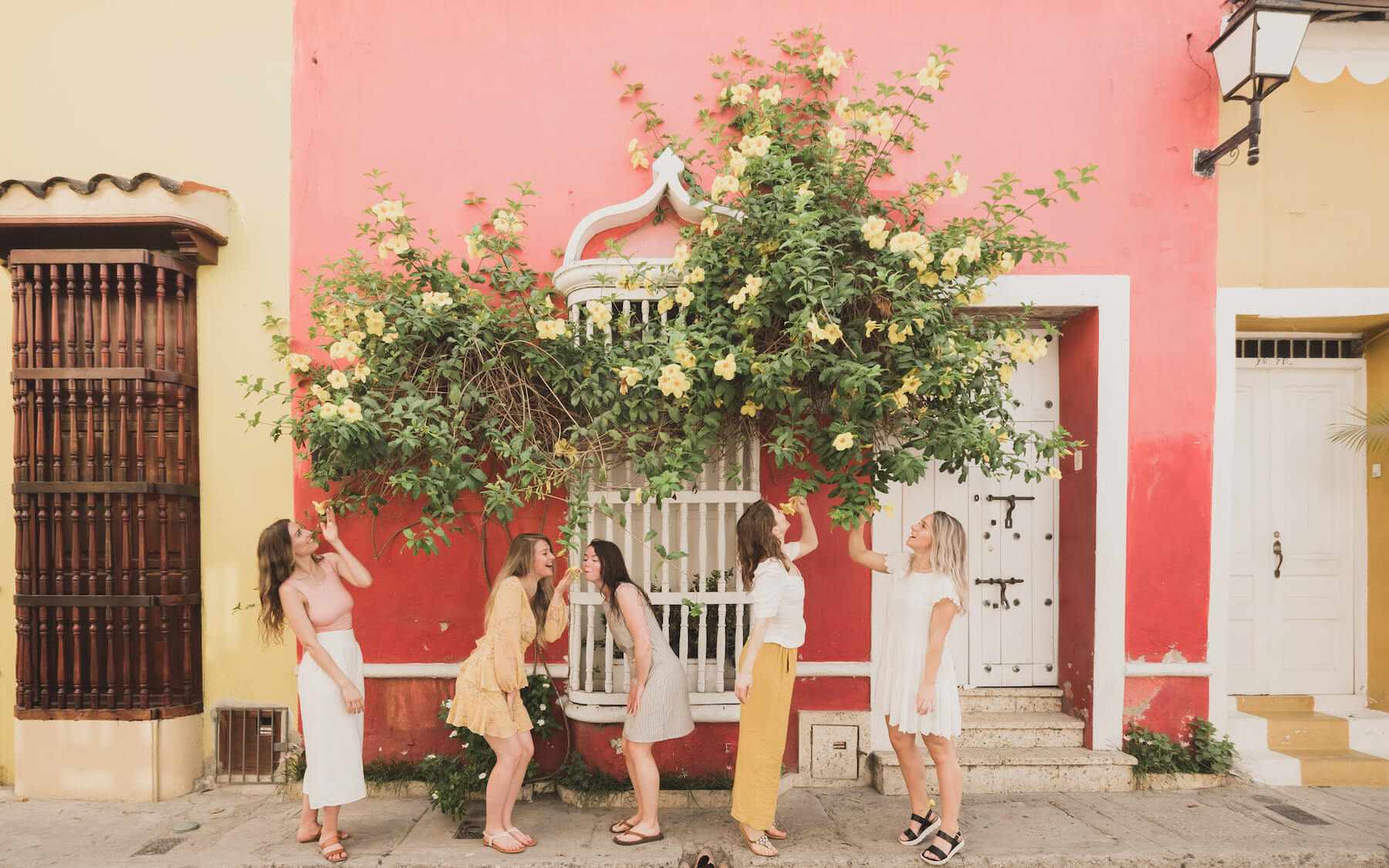 5 girlfriends having fun and smelling flowers on the streets of Cartagena, Colombia