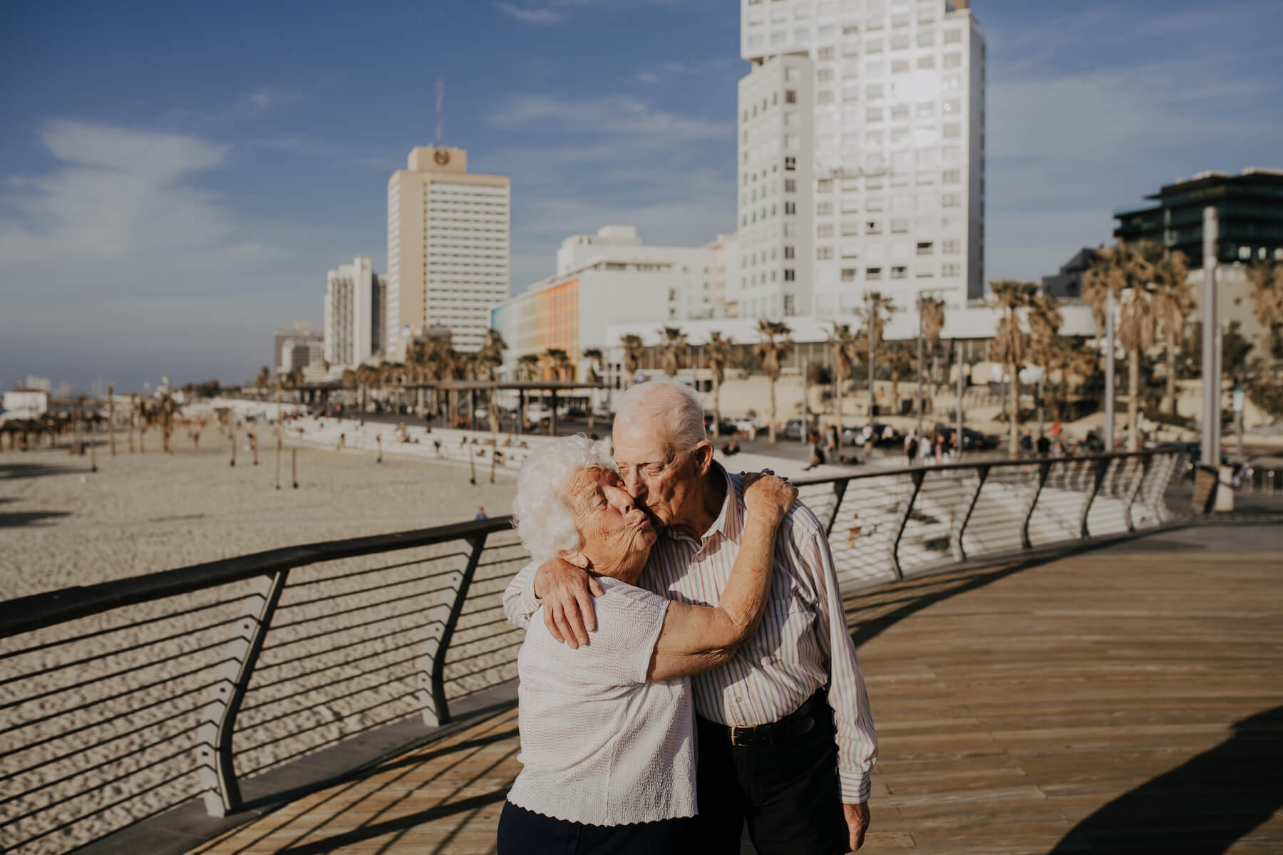 a older couple hugging and the man is giving her a kiss, they're standing on a boardwalk in Tel Aviv, Israel
