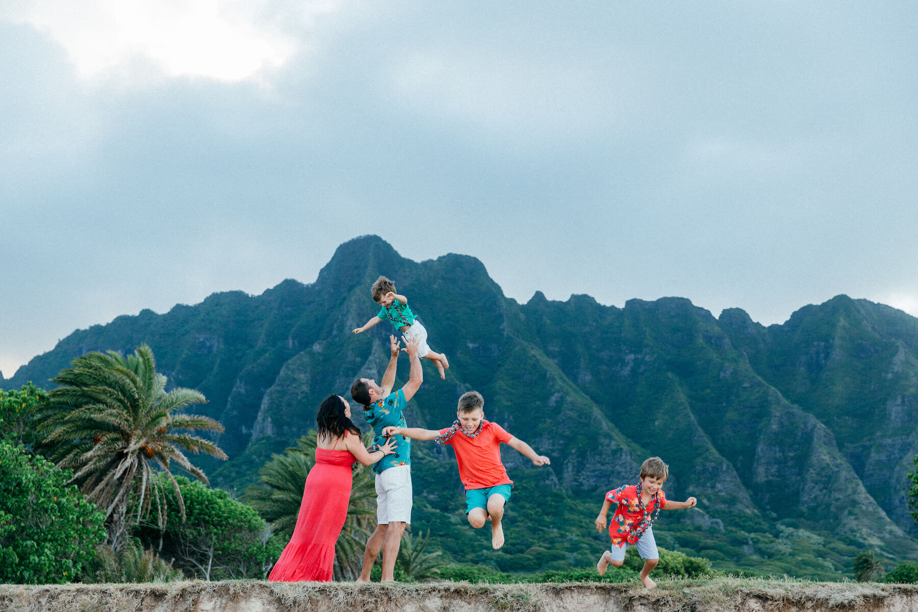 family of five, the three sons are jumping off a small ledge on the beach in Honolulu, Hawaii