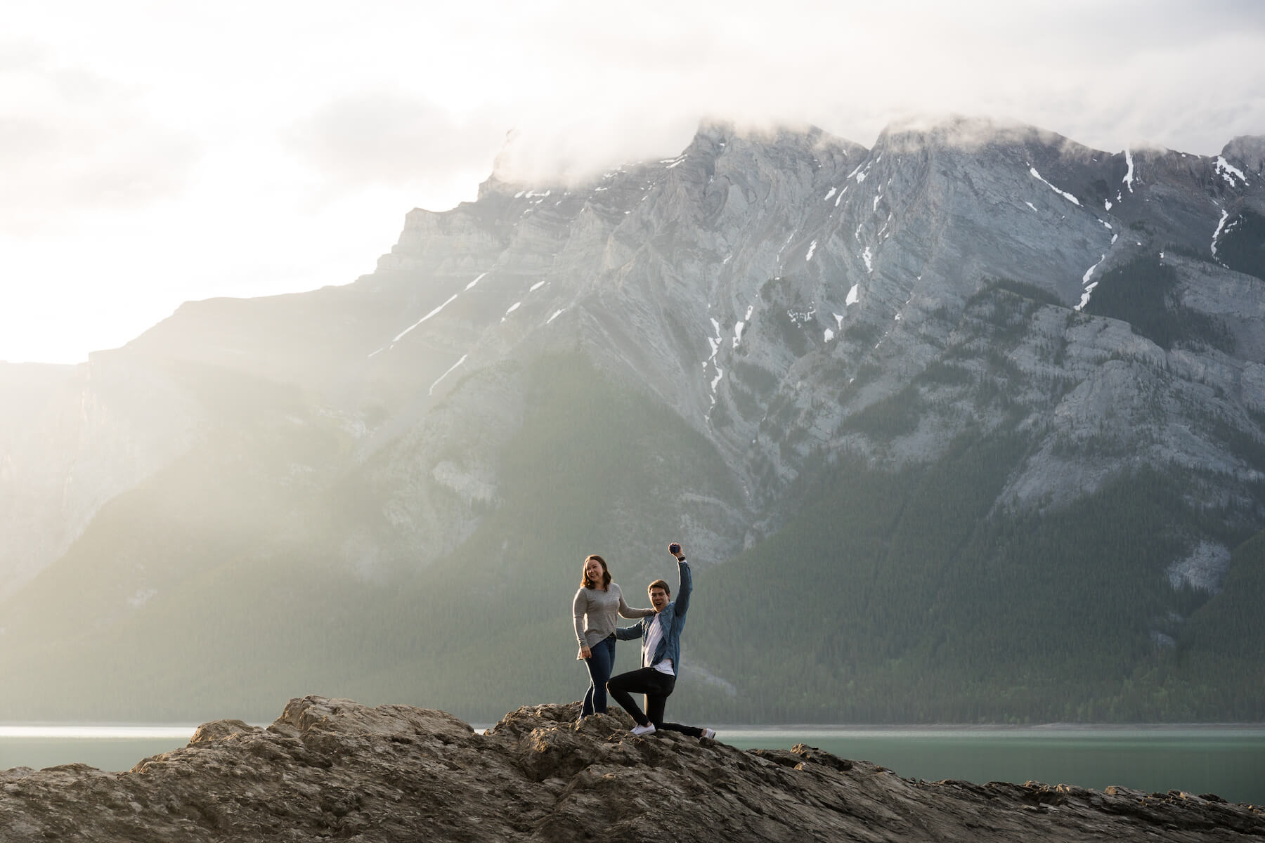 a man is proposing to the woman and he is raising his arms in the air in Banff, Canada