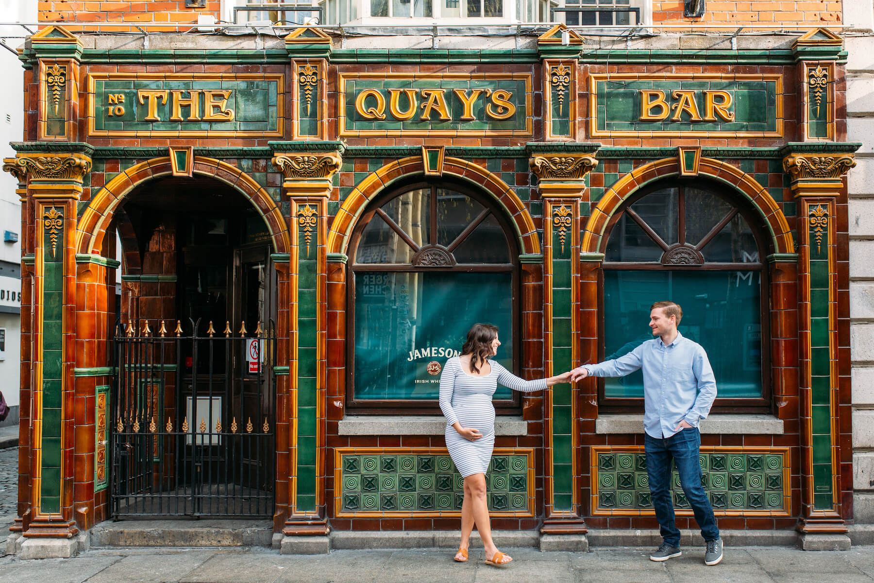 a pregnant couple standing in front of a pub in Dublin, Ireland