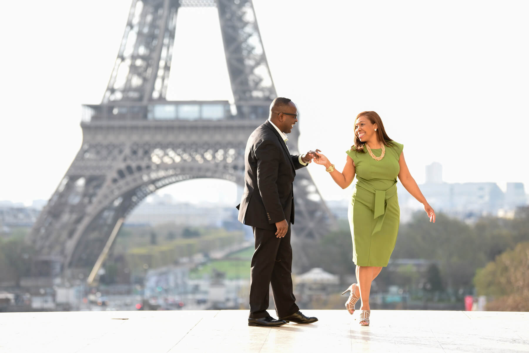 older couple holding hands and dancing with the Eiffel Tower in the background in Paris, France
