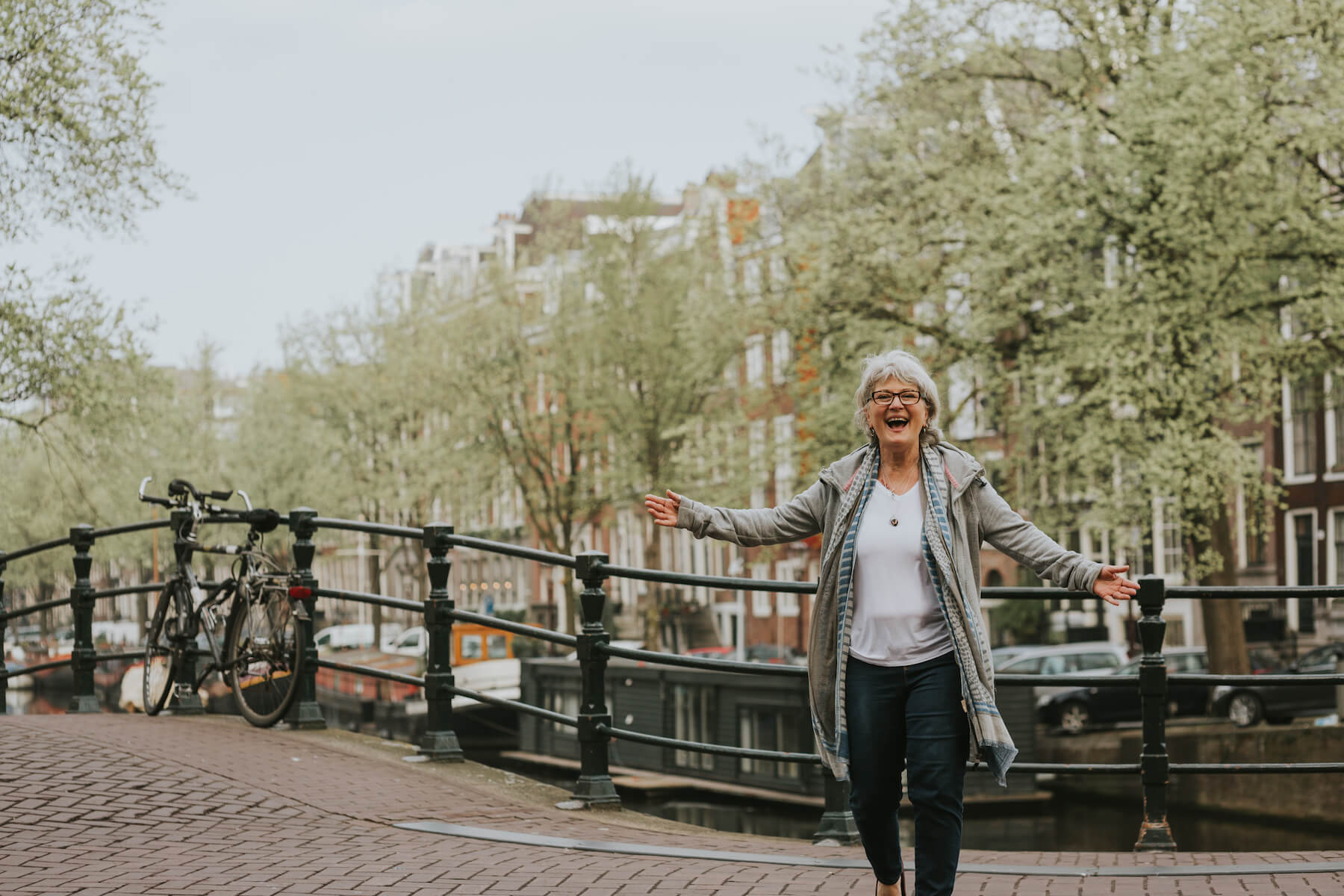 solo traveller standing on a bridge with her hands out in Amsterdam, Netherlands