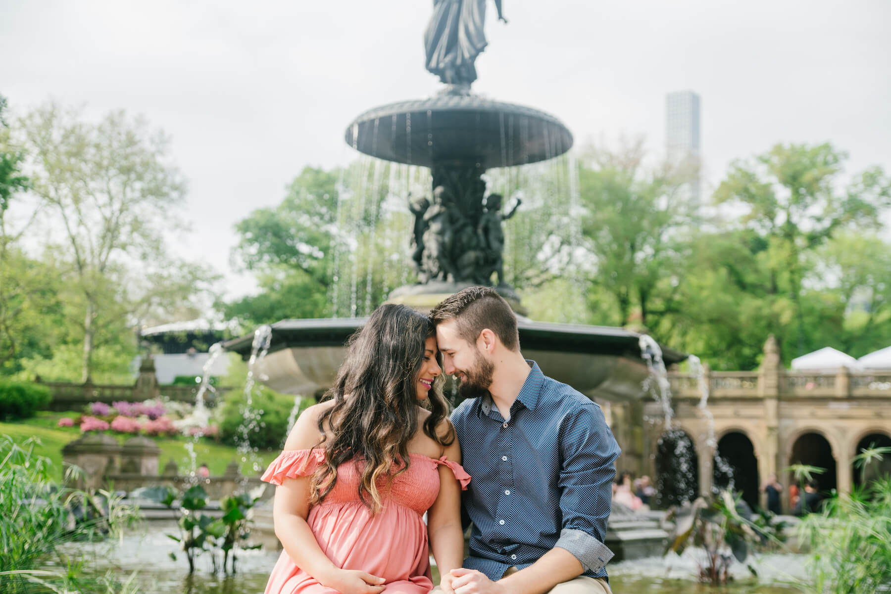 pregnant couple sitting down by a fountain in central park, New York City, New York