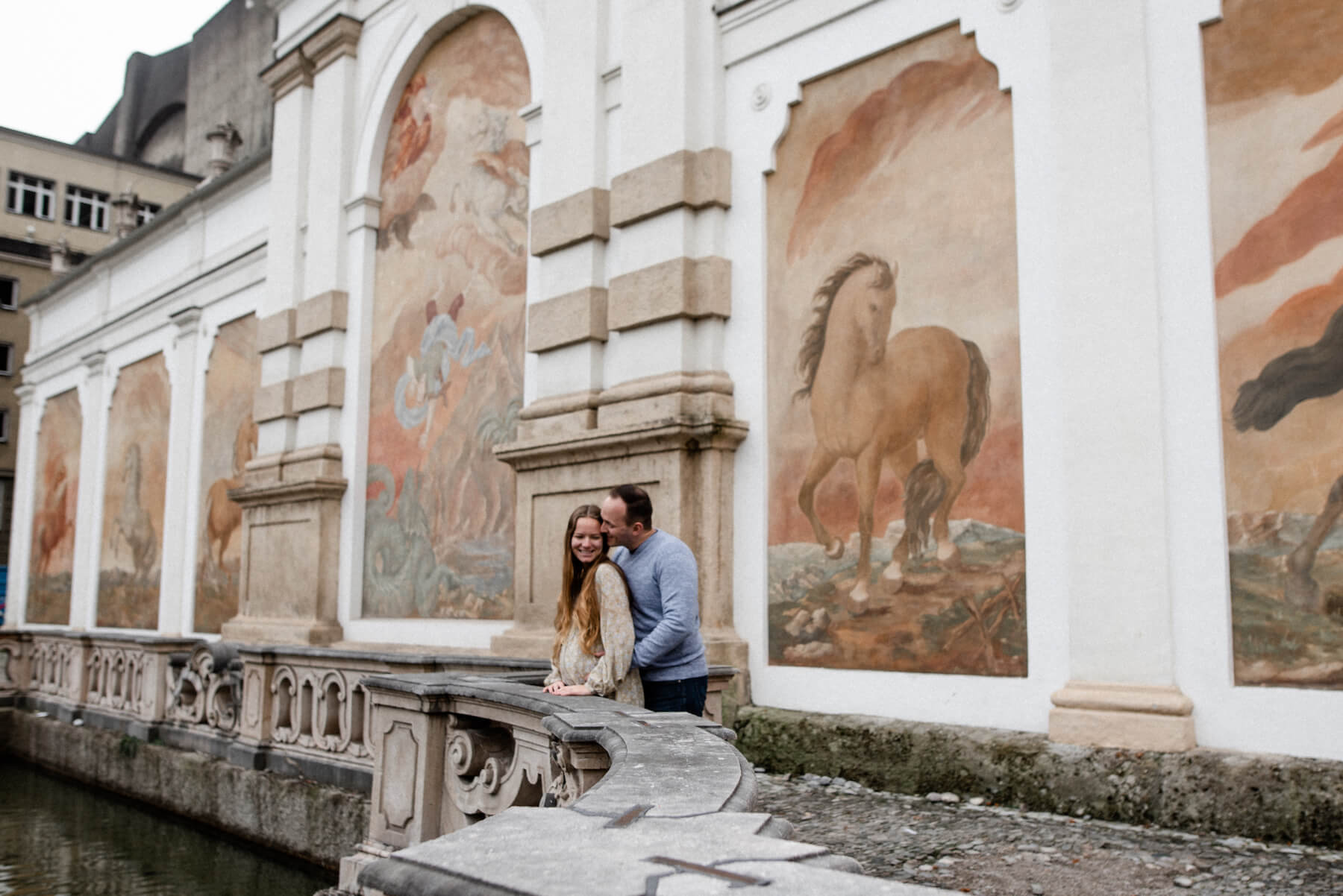 pregnant couple standing in front of mural in Salzburg, Austria