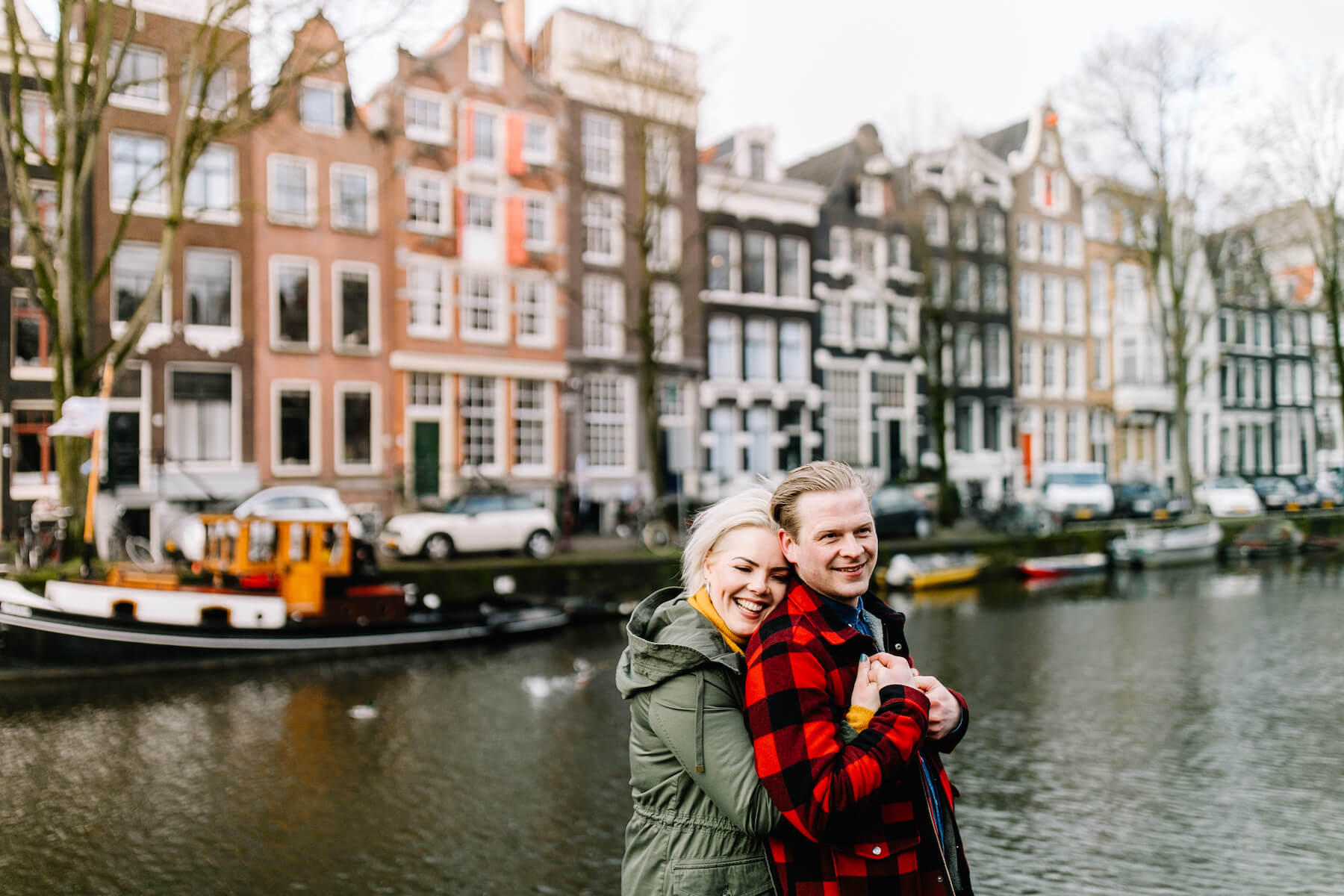 couple holding each other with beautiful row houses in the background in Amsterdam, Netherlands