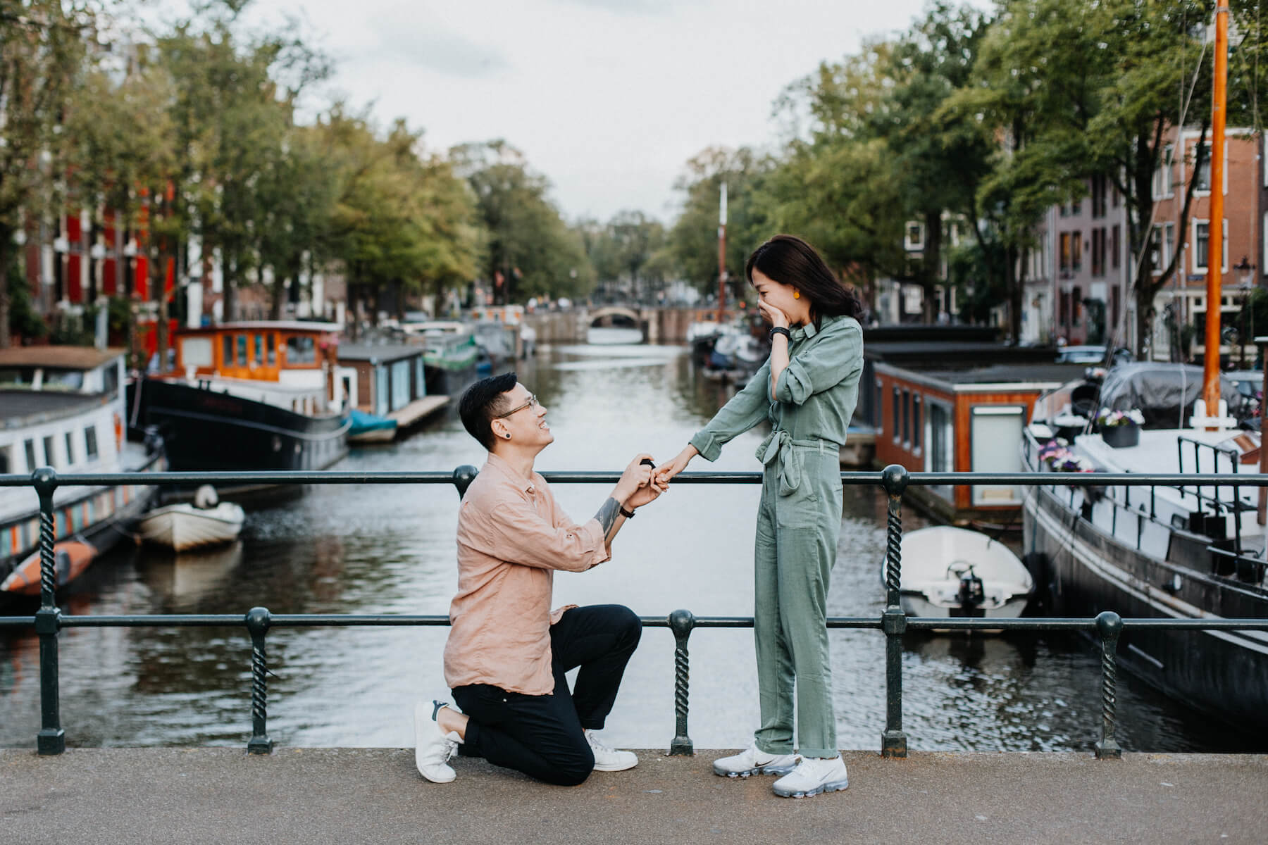 the man is on his knee and proposing to the woman in Amsterdam, Netherlands