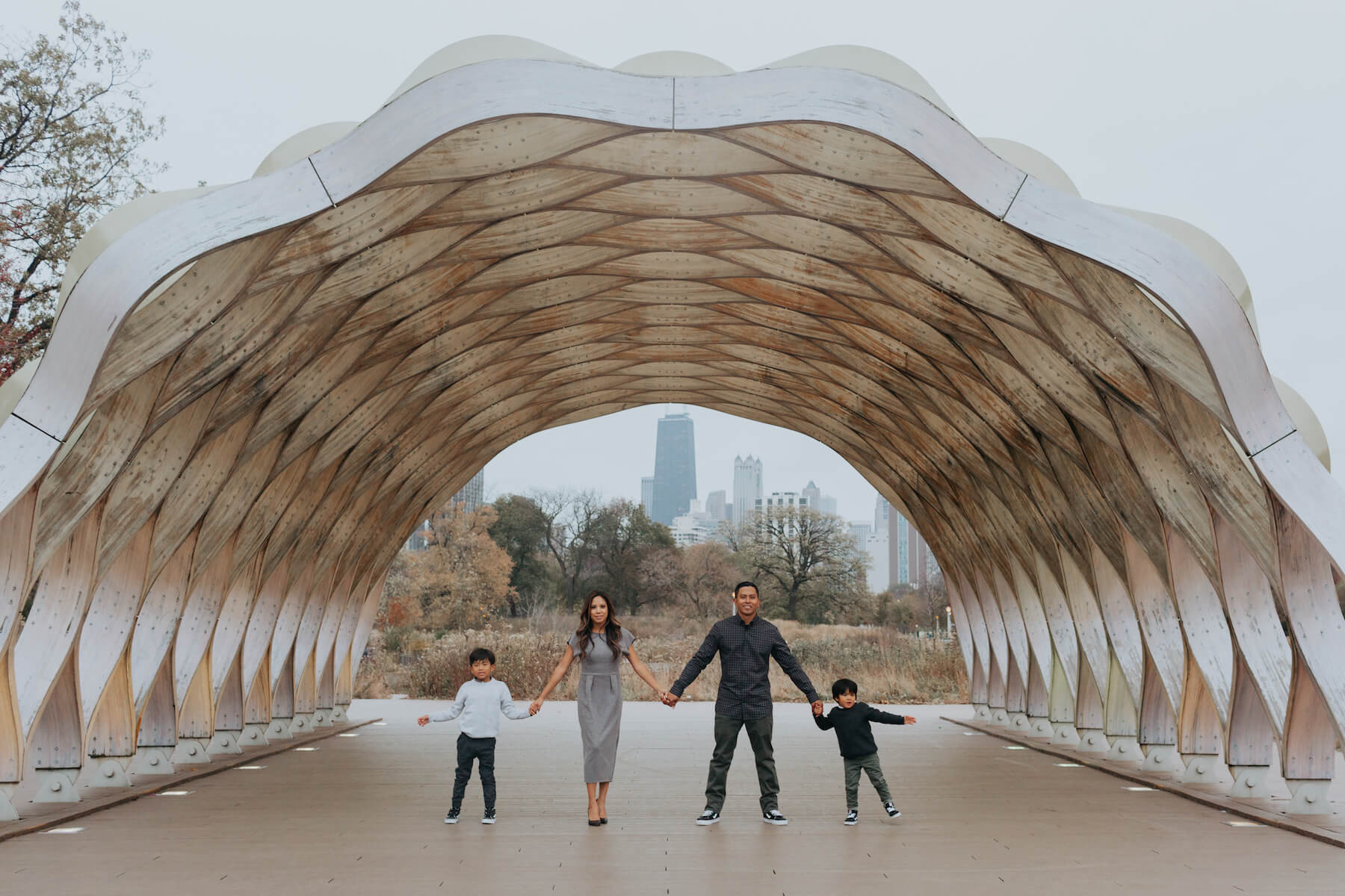 family of four holding hands under a structure in Chicago, Illinois, United States of America