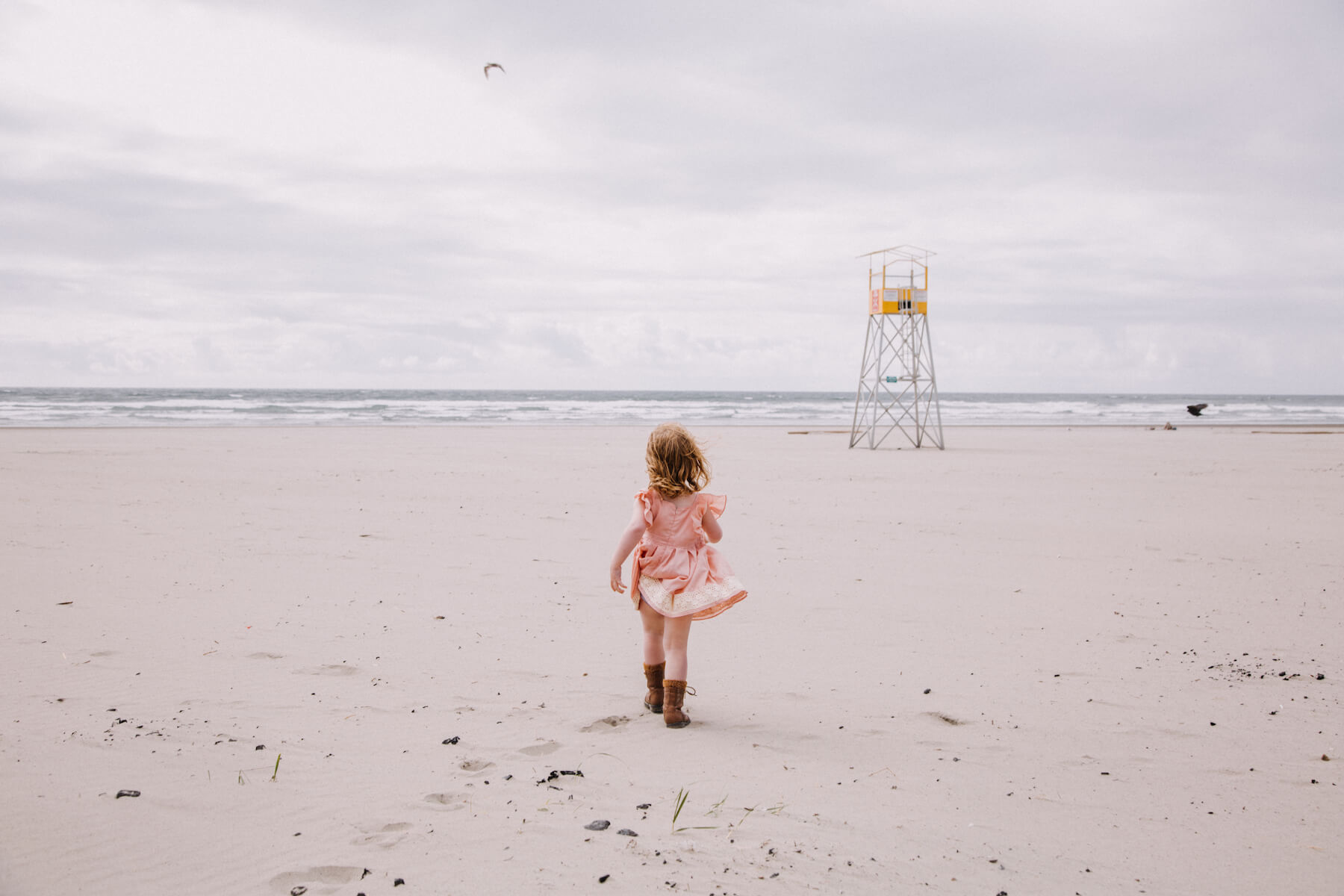 small girl walking on the beach towards the ocean in Portland, Oregon
