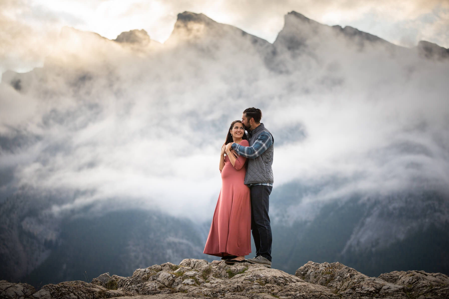 pregnant couple holding each other in an embrace near the lake in Banff, Alberta, Canada