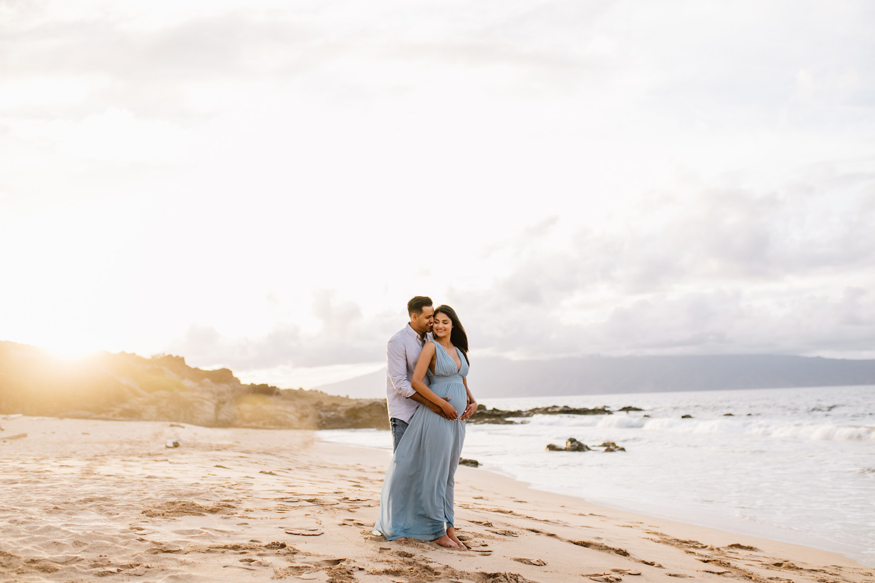 pregnant couple holding each other on the beach in Maui, Hawaii
