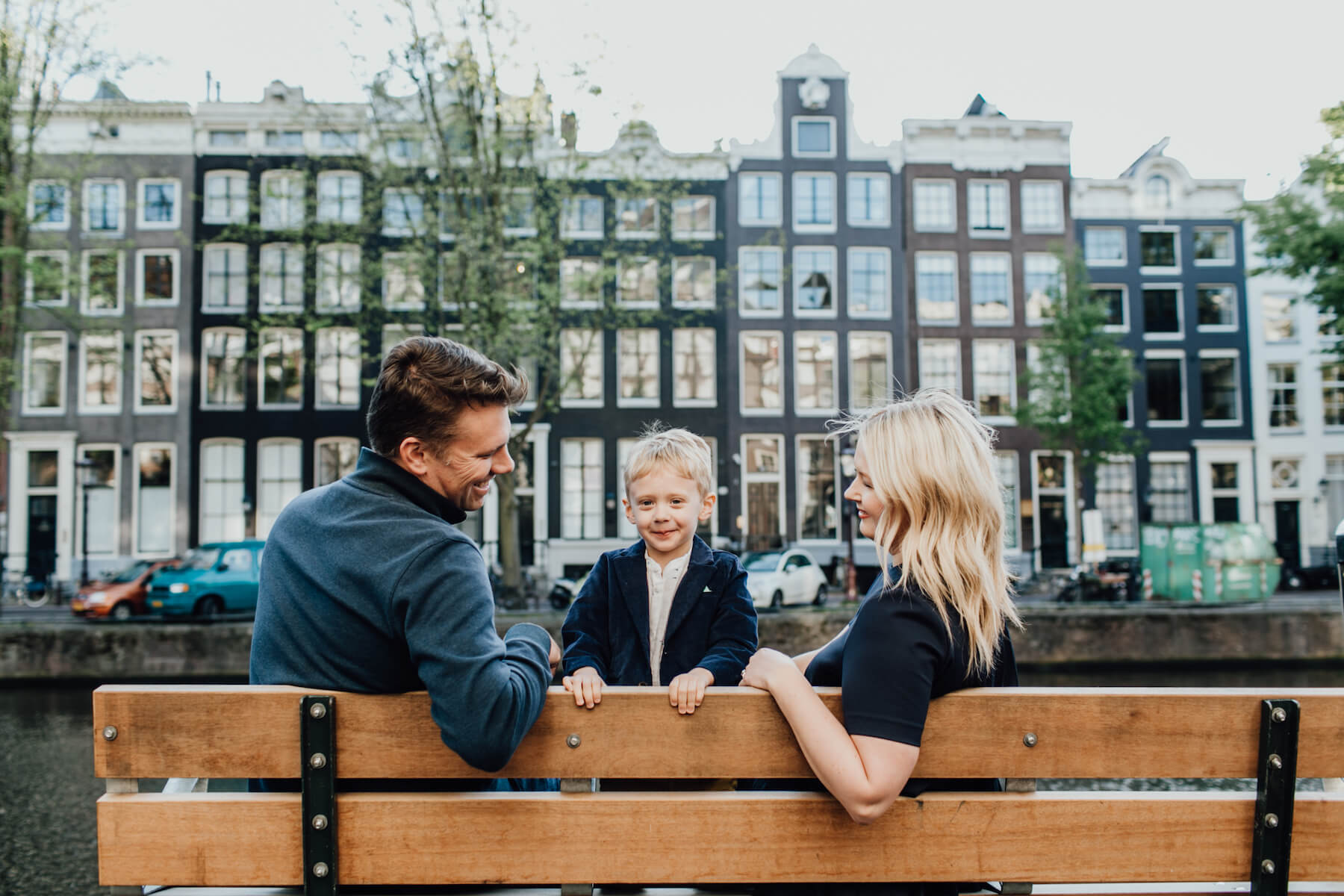 family sitting on a bench near the canal in Amsterdam, Netherlands