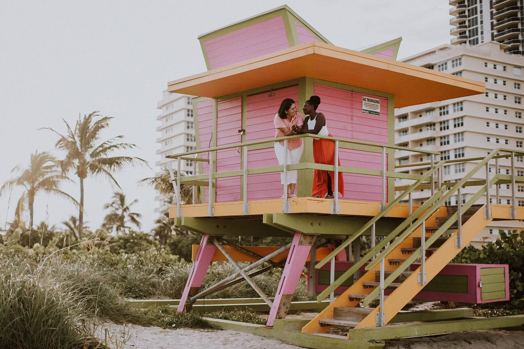 LGBTQ couple looking at each other while standing a lifeguard tower in Miami, Florida