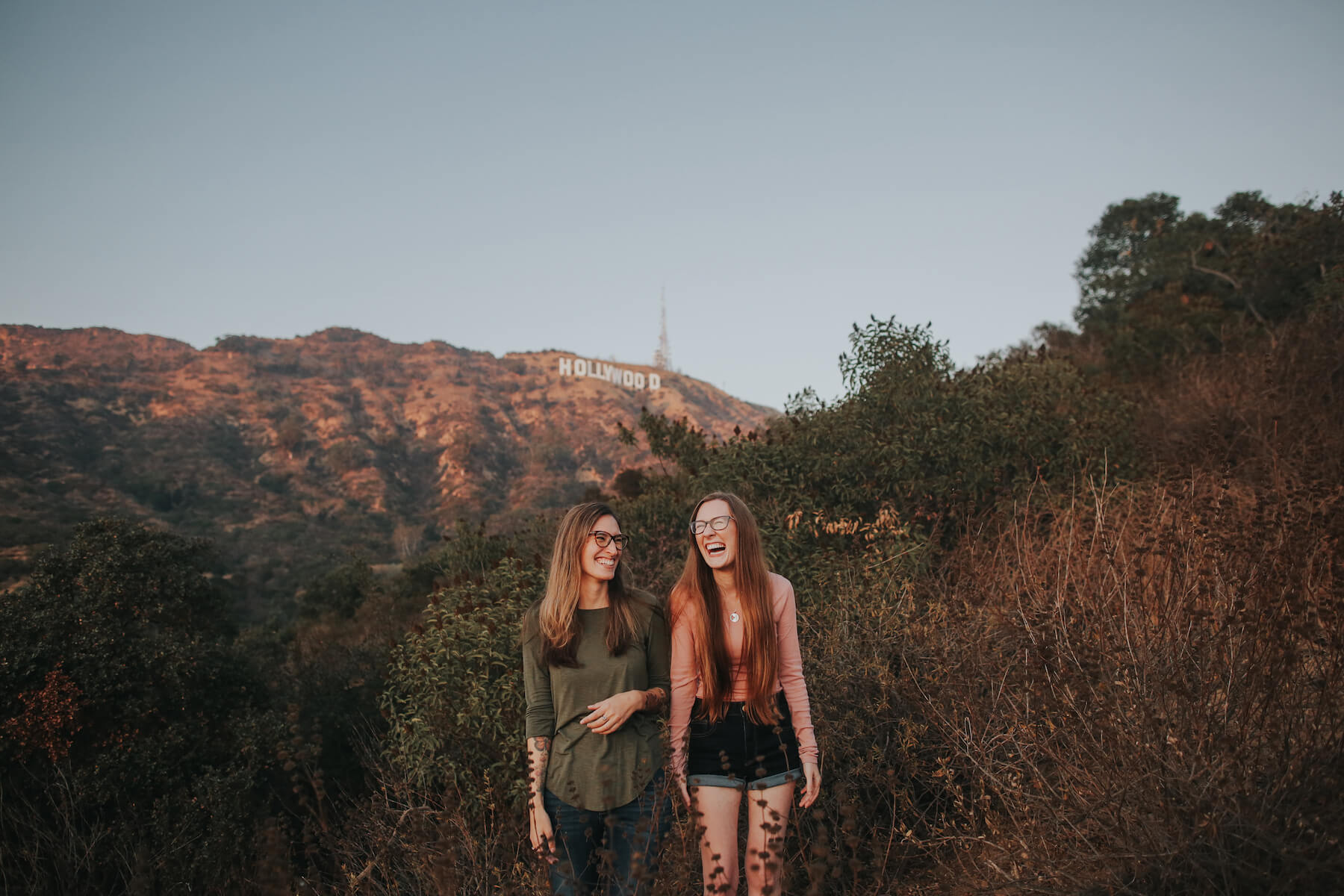 two girls standing and laughing with the Hollywood sign in the background in Los Angeles, California