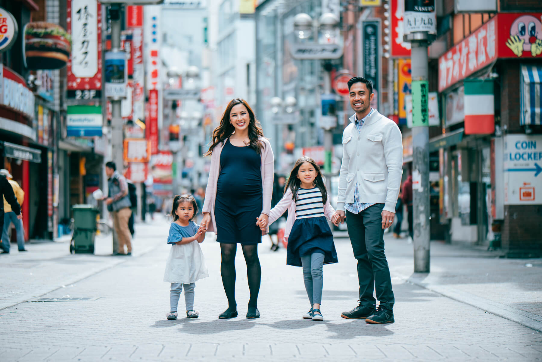 a family of 4, and the mother is pregnant, standing on the street holding hands in Tokyo, Japan