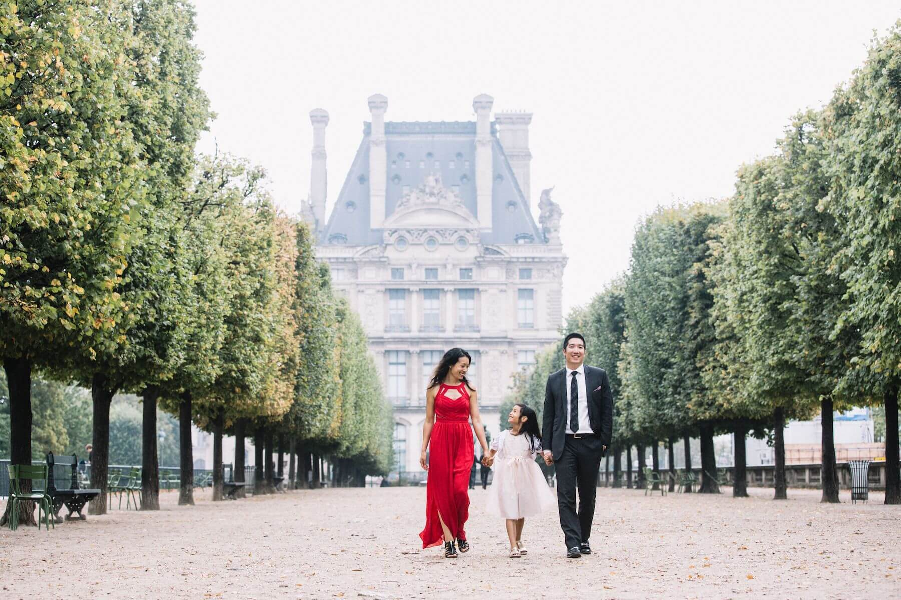 a family of three holding hands and walking in the gardens near the Louvre in Paris, France