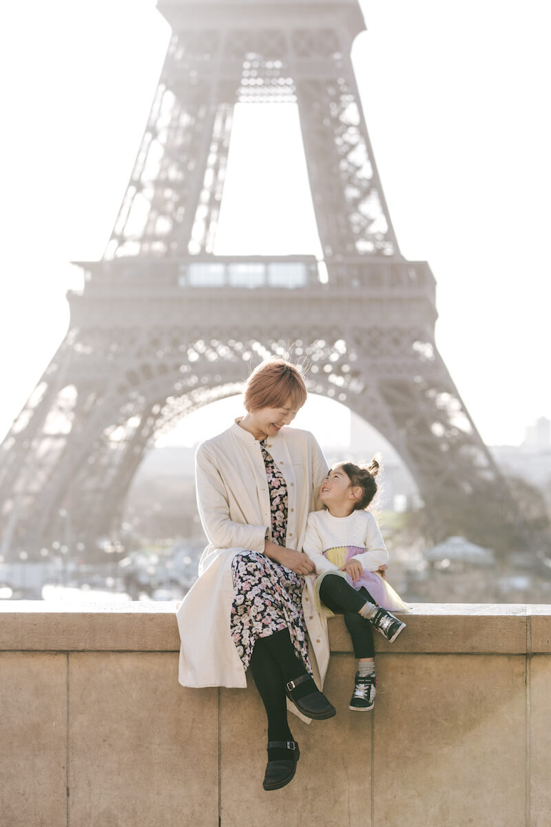 mother and daughter sitting on a ledge and behind them is the Eiffel Tower in Paris, France