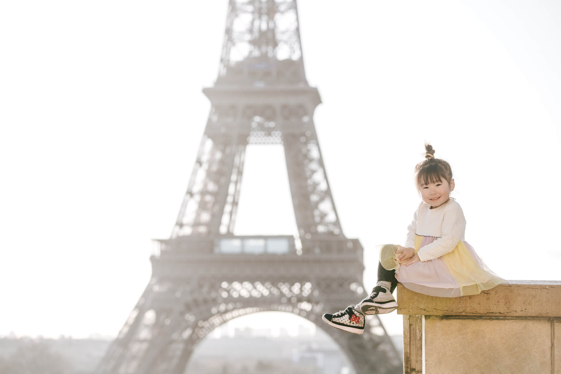 a small girl sitting on a ledge with the Eiffel Tower in the background in Paris, France