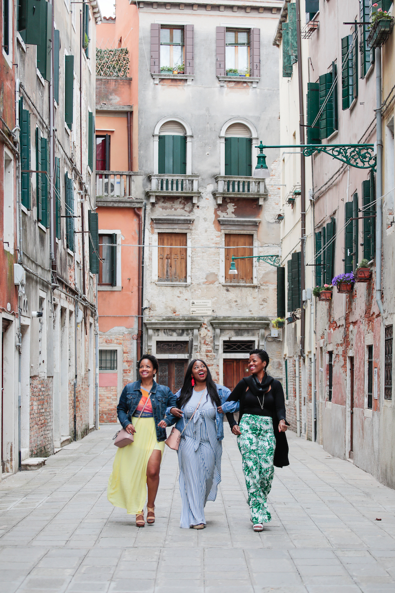 3 sisters walking through narrow streets near the canal in Venice, Italy