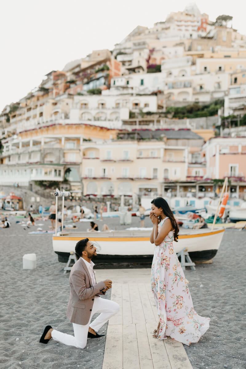 couple in Positano, the man is proposing to the woman on the beach in Positano, Italy