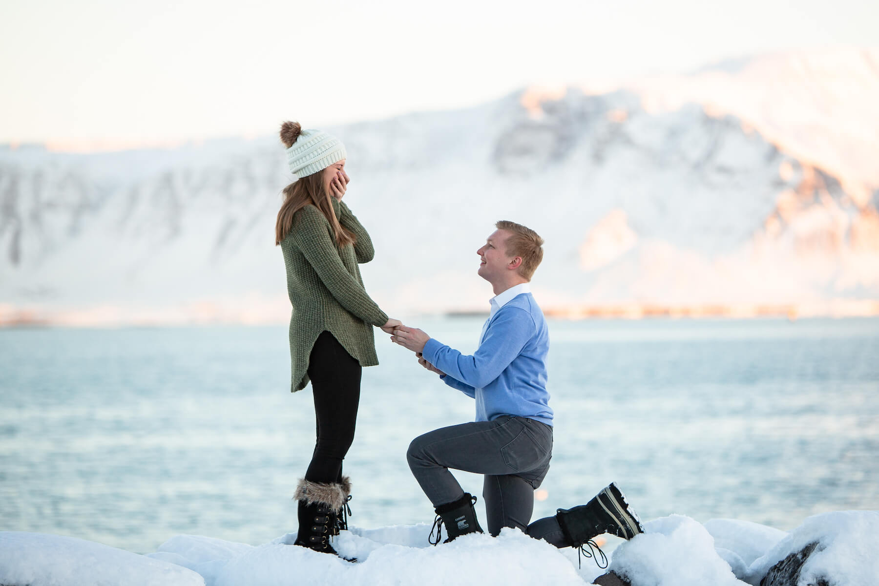 a man is proposing to the woman, standing in the snow in Reykjavik, Iceland