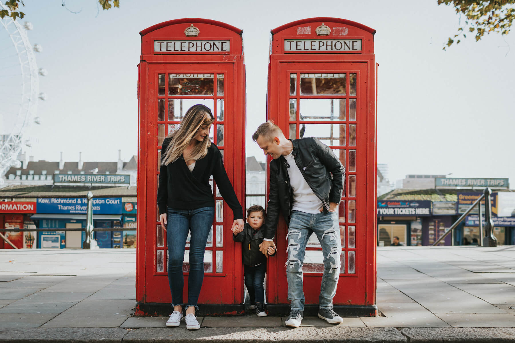 a family of three standing by a red phone booth in London, England