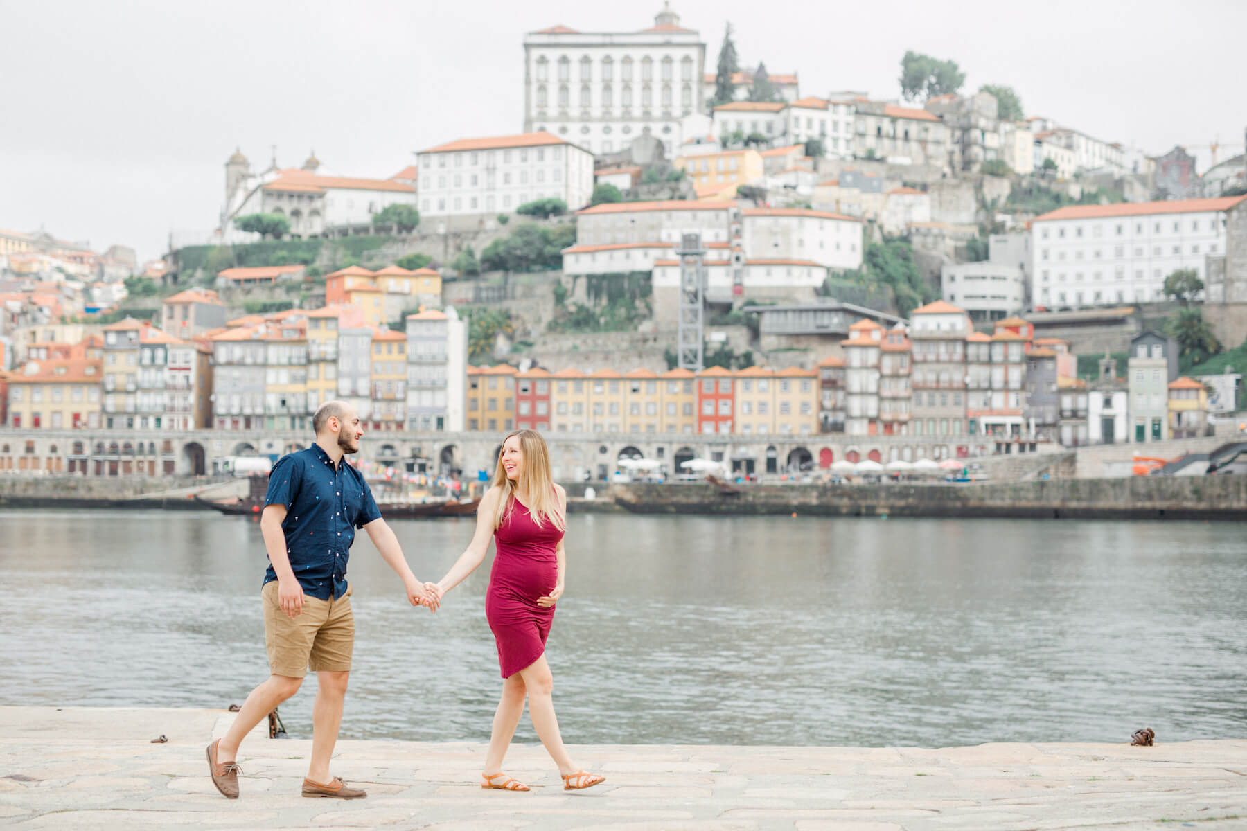 pregnant couple holding hands and walking in Porto, Portugal