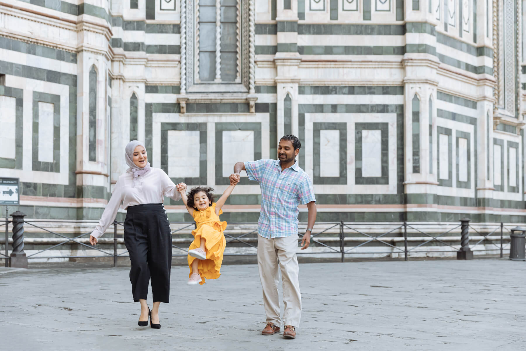 family of three, the girl is being swung in front of the Duomo in Florence, Italy