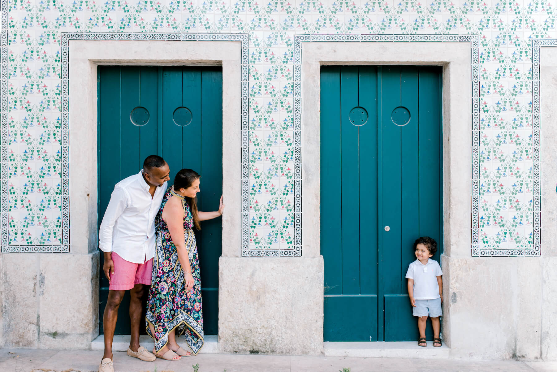 family of three standing in front of a colorful building, the boy is being playful and trying to hide in Lisbon, Portugal