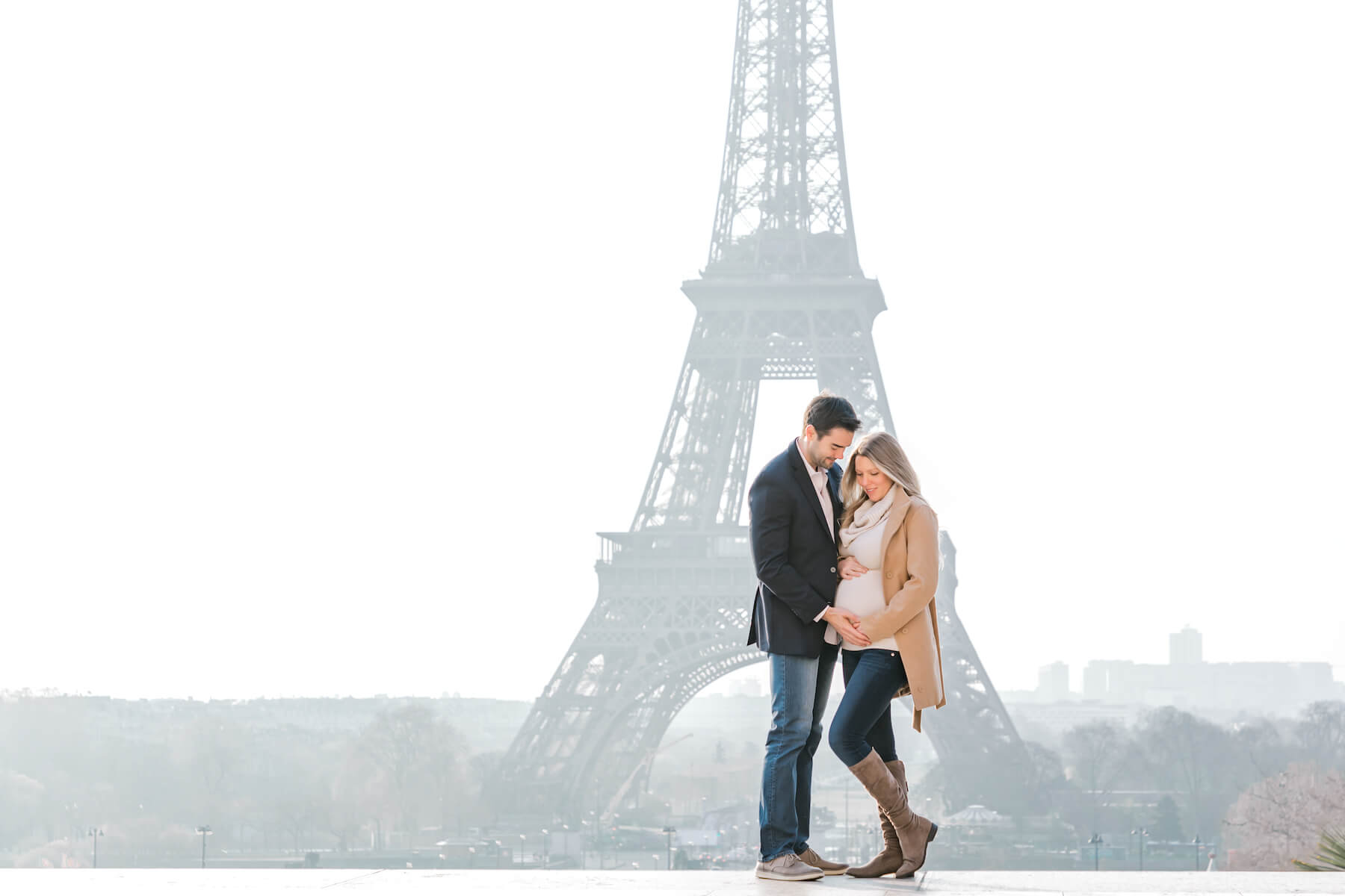 pregnant couple in looking at the woman's belly in front of the Eiffel Tower in Paris, France