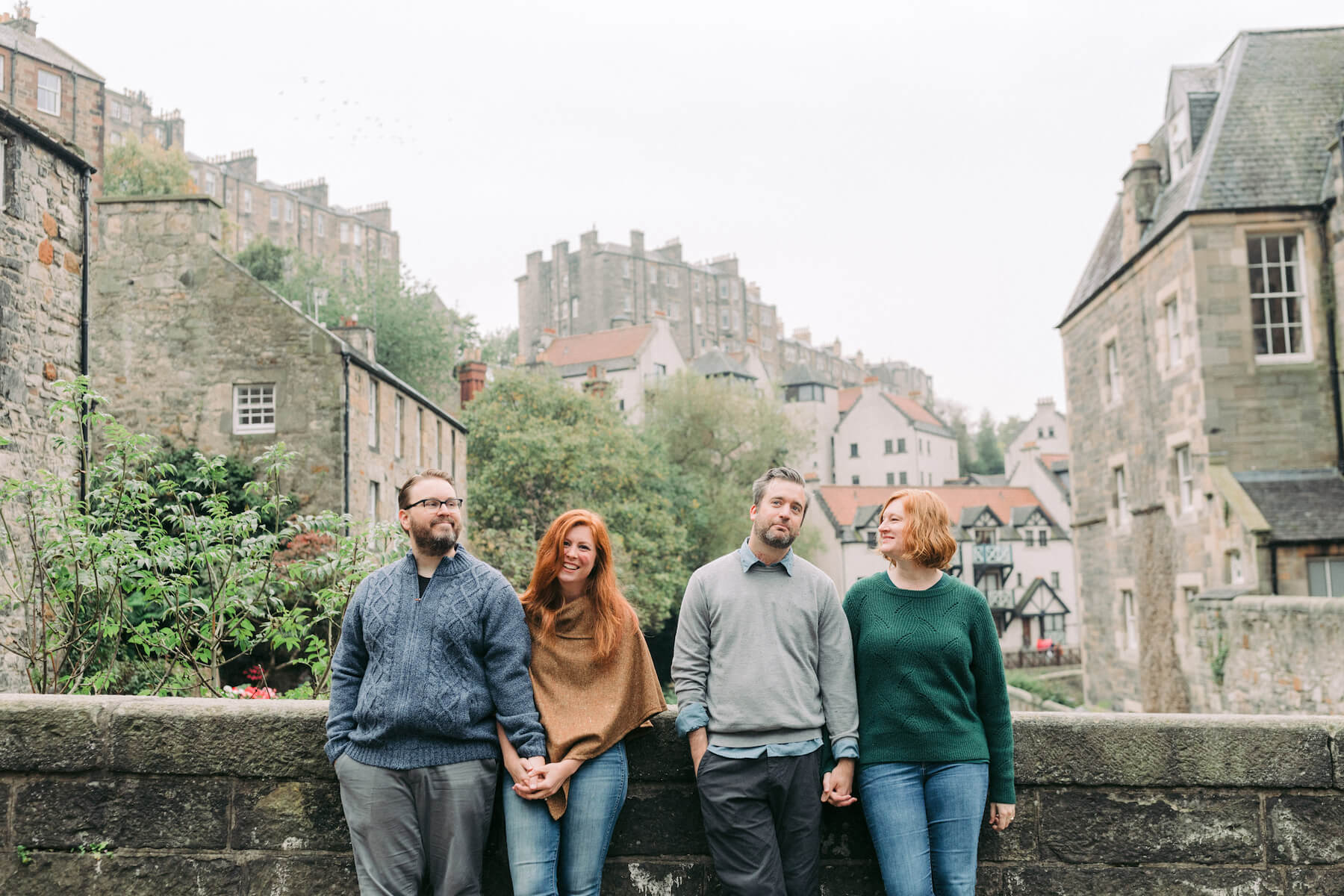 2 couples sitting on stone wall in the town of Edinburgh, UK