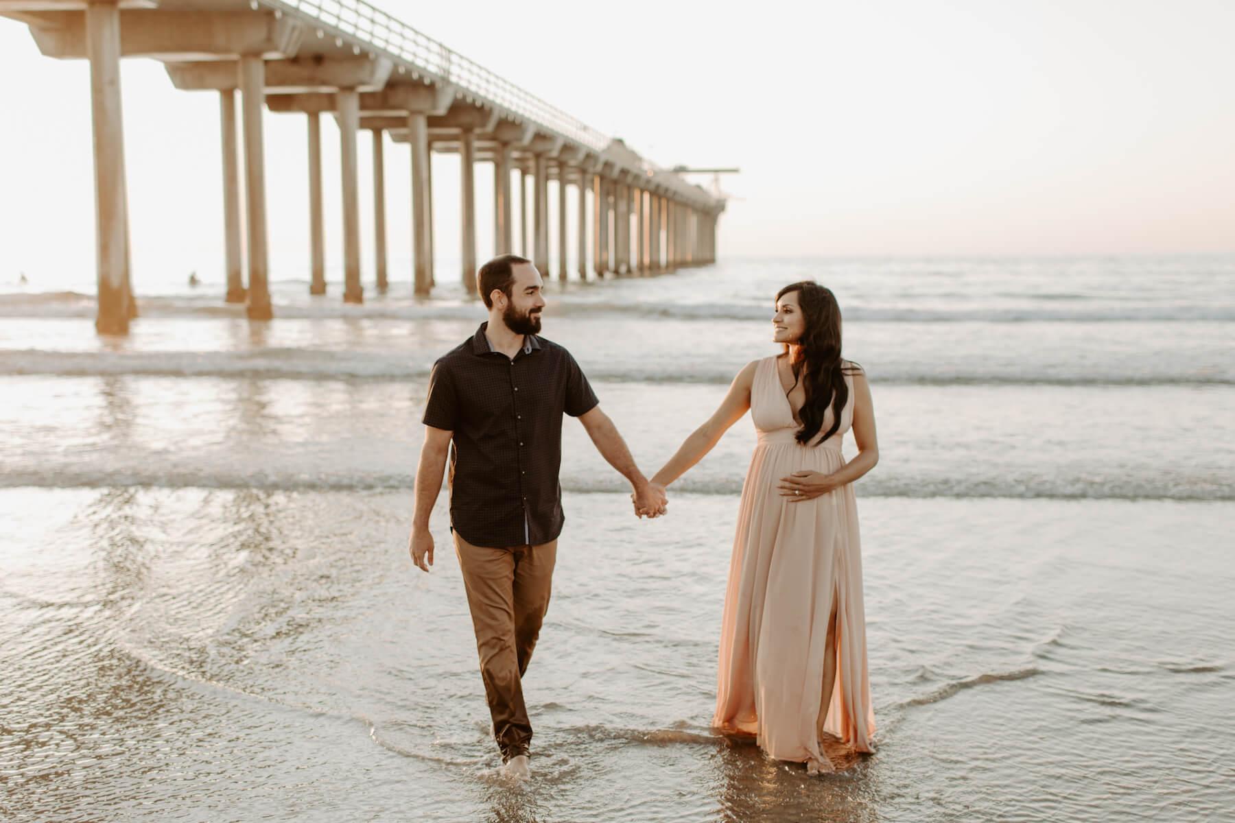 pregnant couple standing on the beach near the ocean in San Diego, California