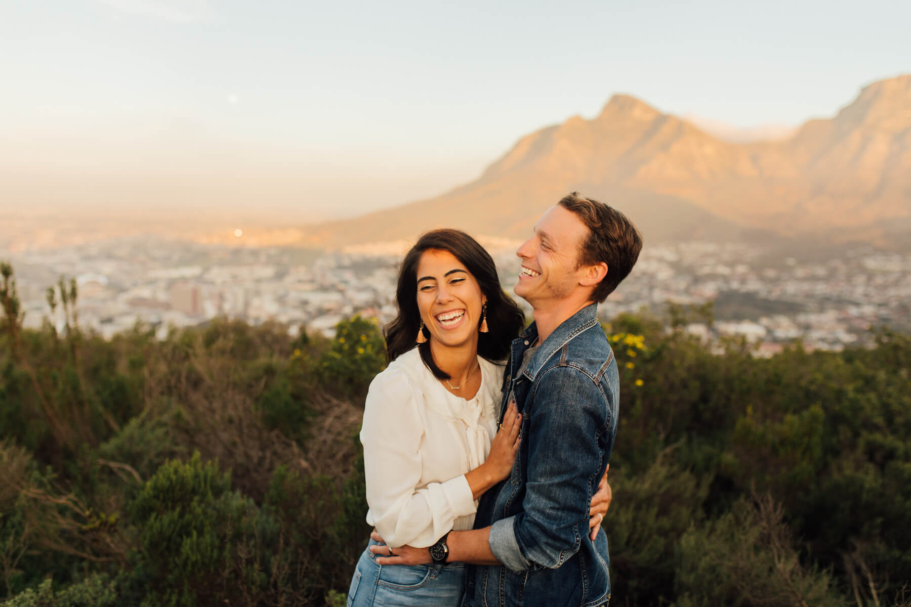 couple holding each other and laughing on a hill in Cape Town, South Africa