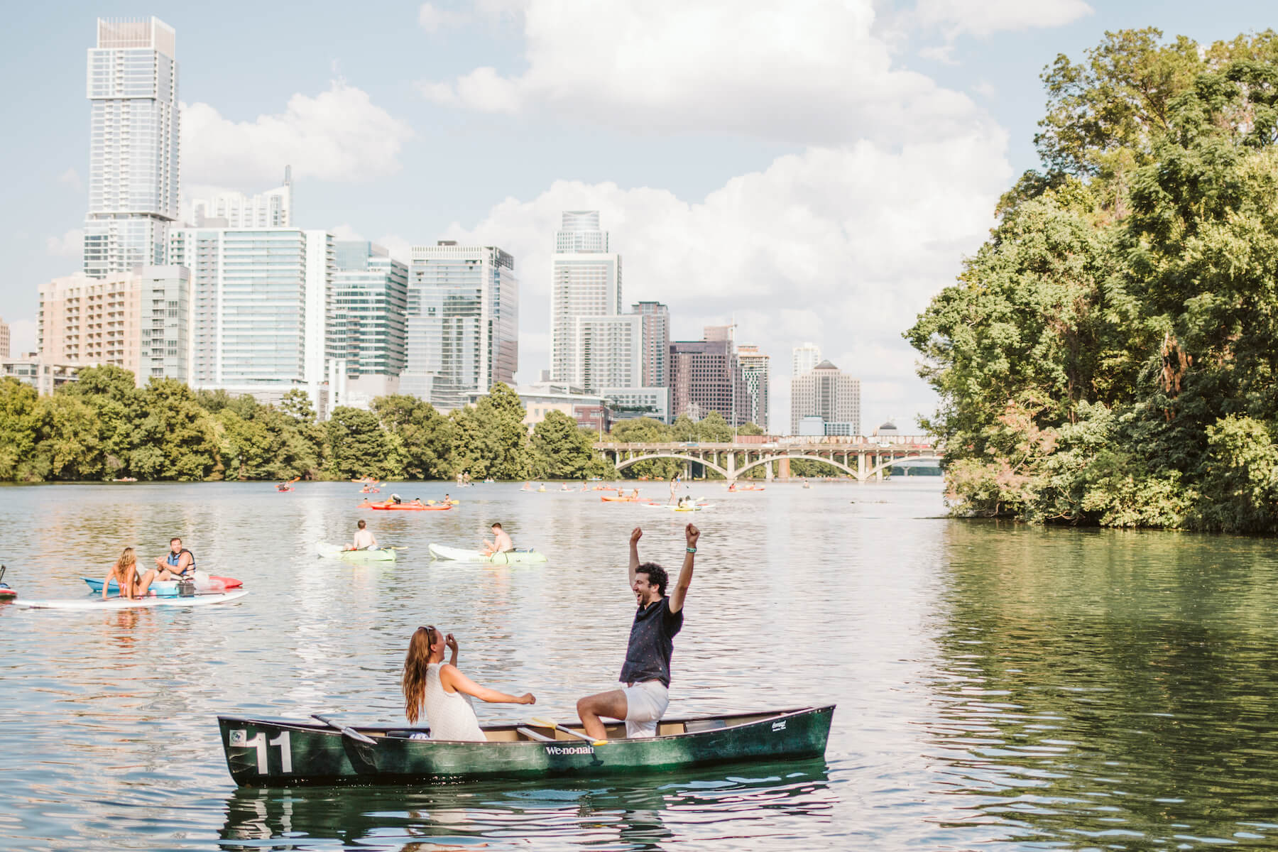 couple in a row boat, the man has his hands in the air, he just proposed to the woman in Austin, Texas