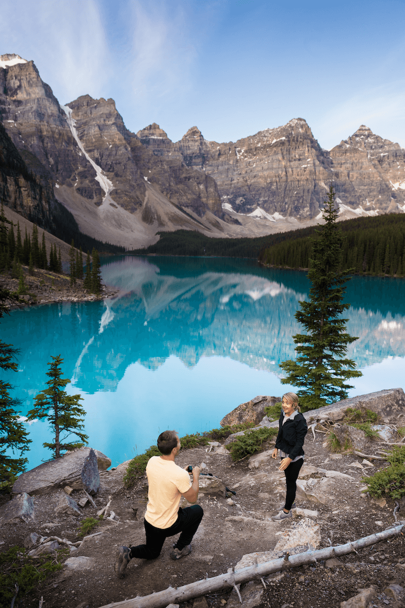 man proposing to a woman standing on a hilltop with a beautiful lake in the background in Banff, Alberta, Canada