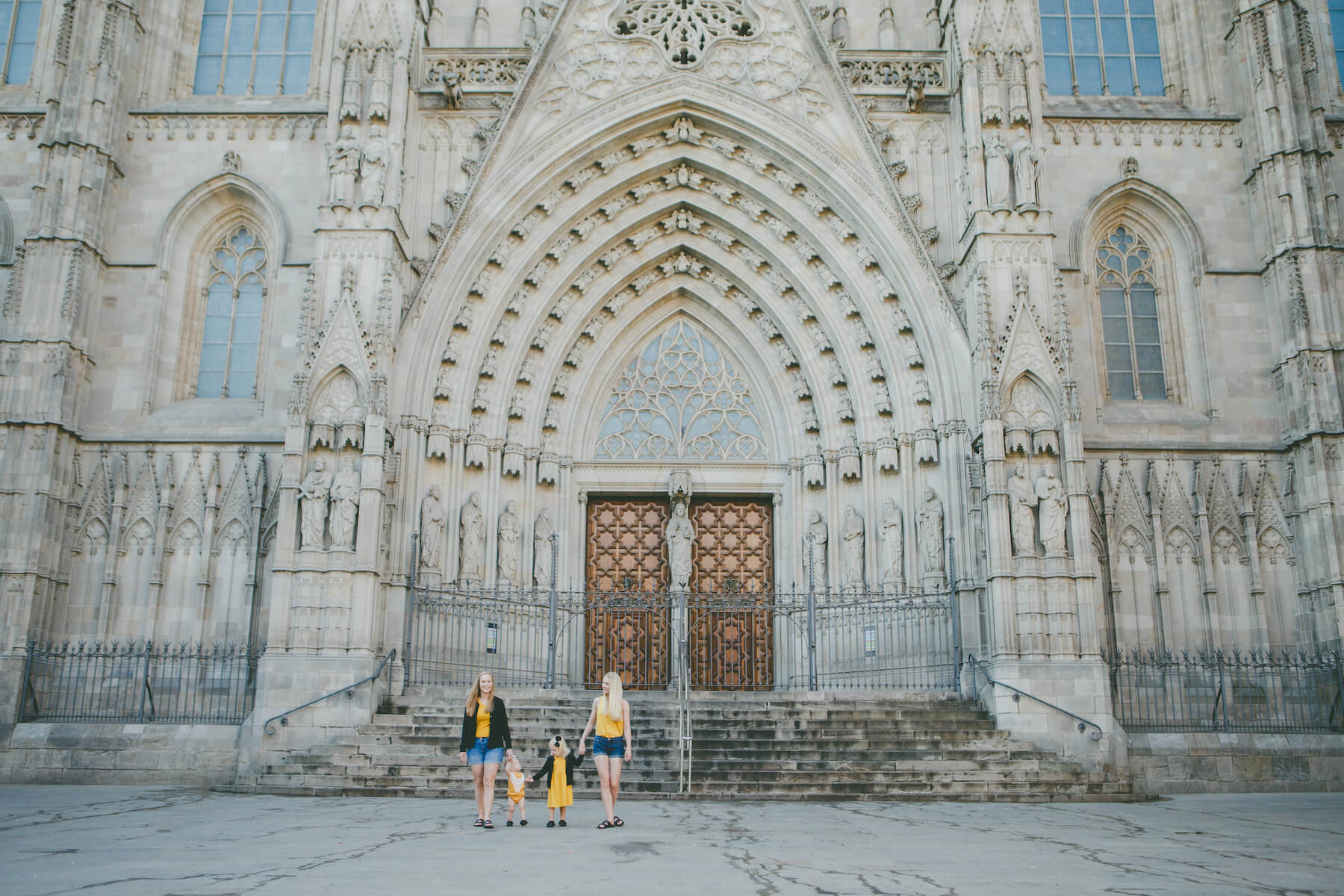 LGBTQ family of four standing in front of a church in Barcelona, Spain