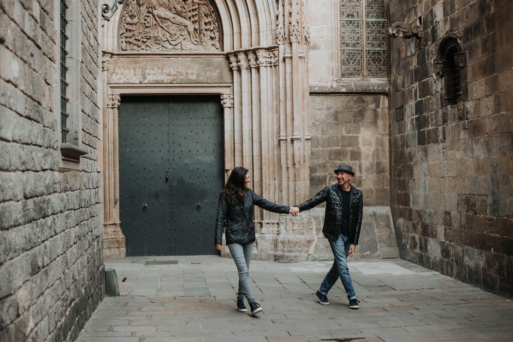 couple holding hands and running through a courtyard full of pigeons in the Gothic District in Barcelona, Spain