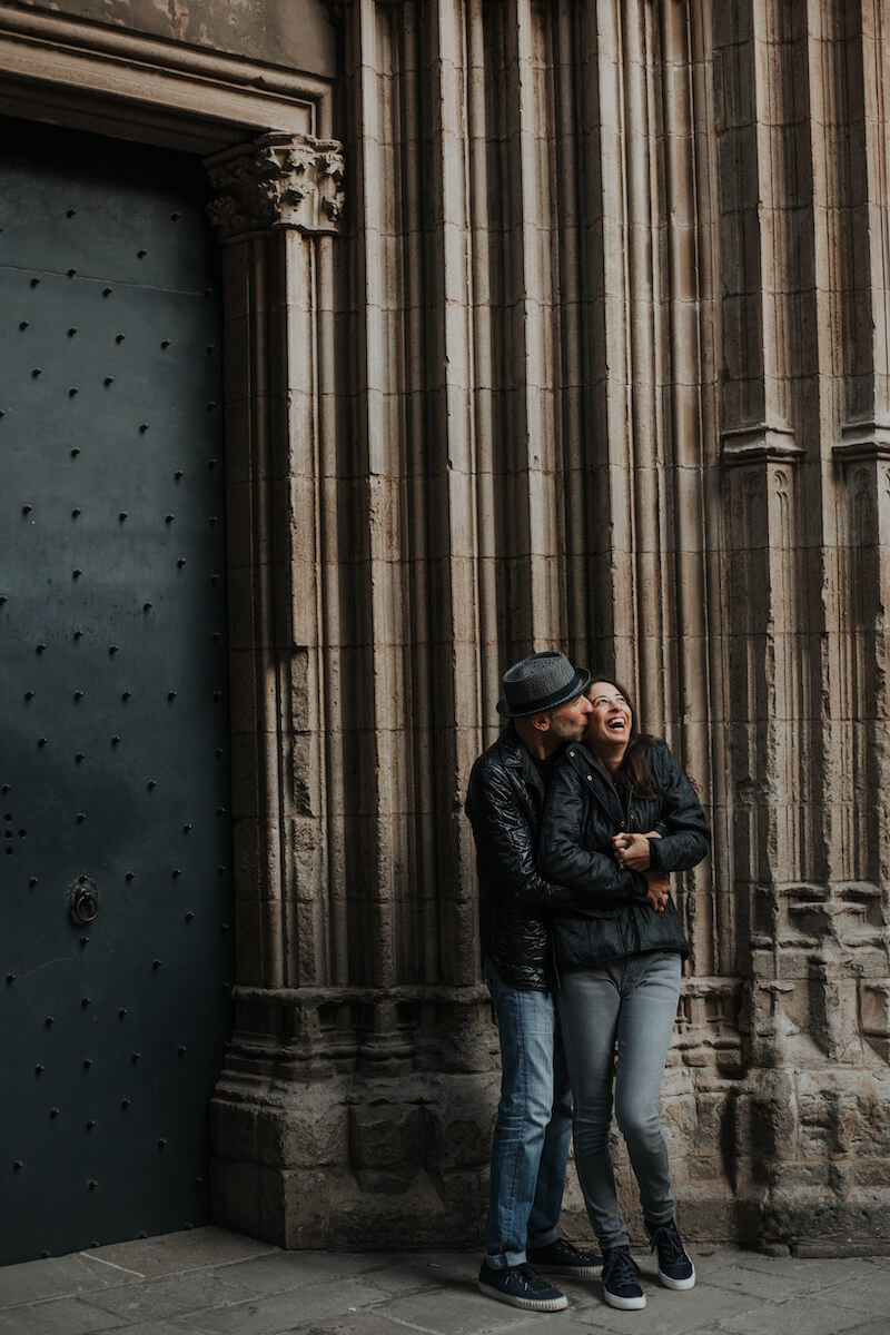 couple hugging each other and standing in front of church door in Barcelona, Spain