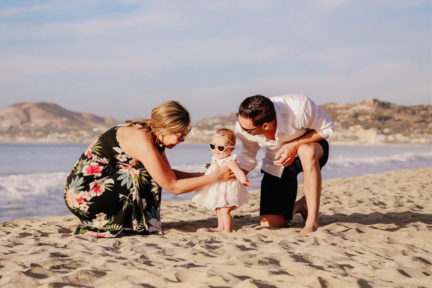 family of three, the baby is wearing sunglasses and sitting on the beach in Cabo San Lucas, Mexico