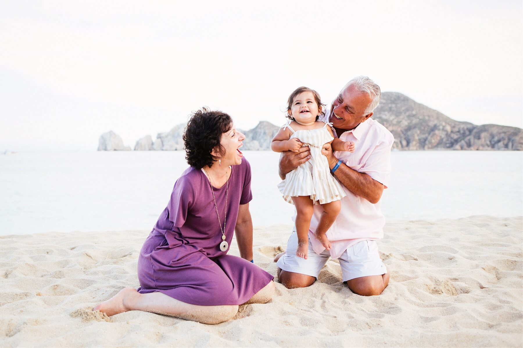 grandparents with young child on the beach in Cabo San Lucas, Mexico