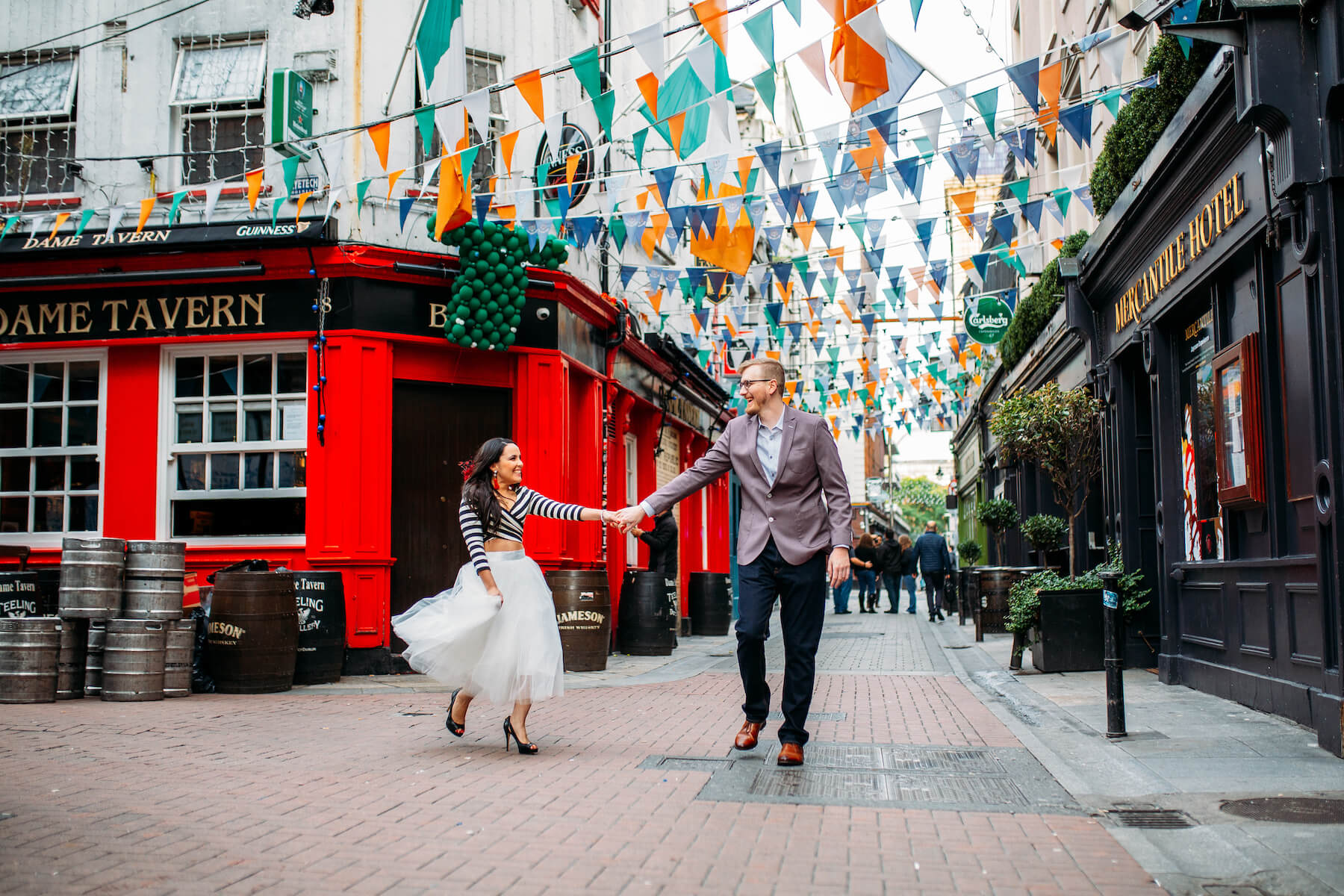 couple holding hands and dancing in front of a pub in Dublin, Ireland