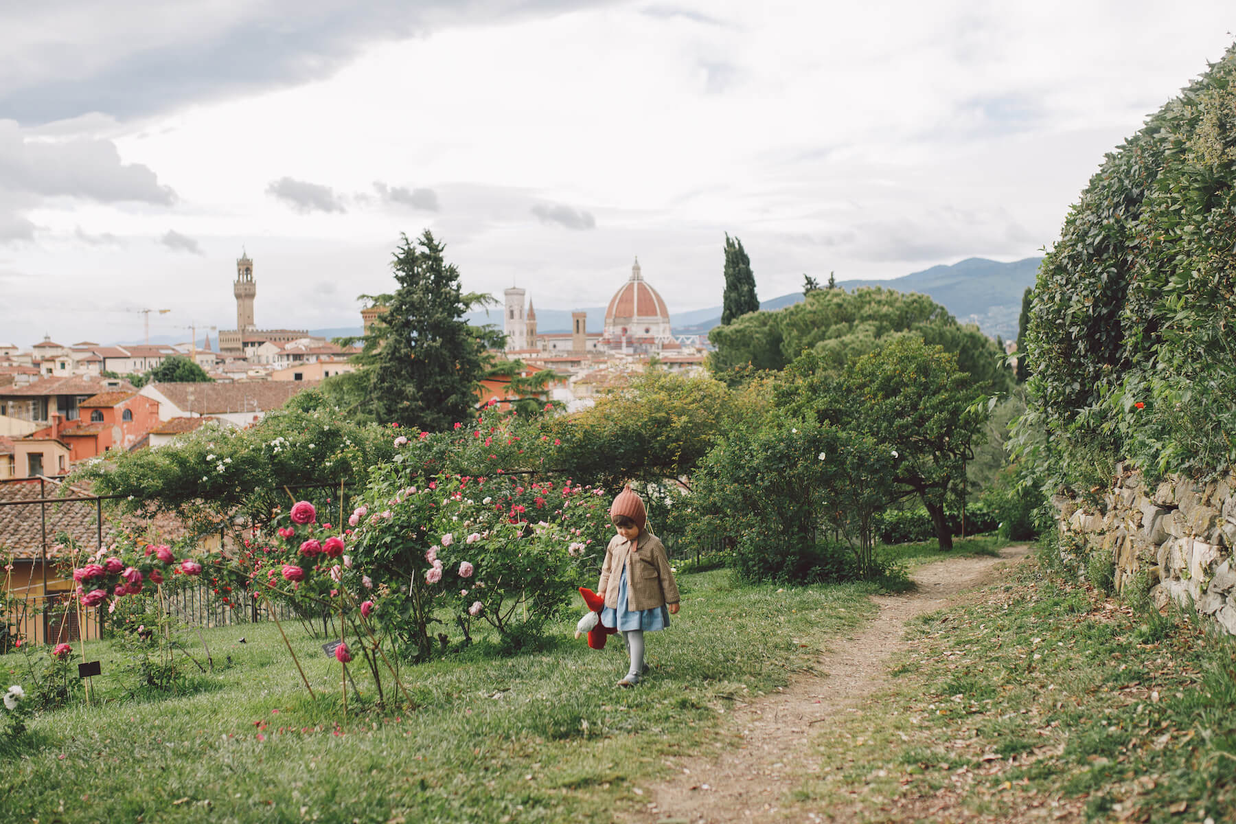 a little girl is holding a toy and walking in a garden in Florence, Italy