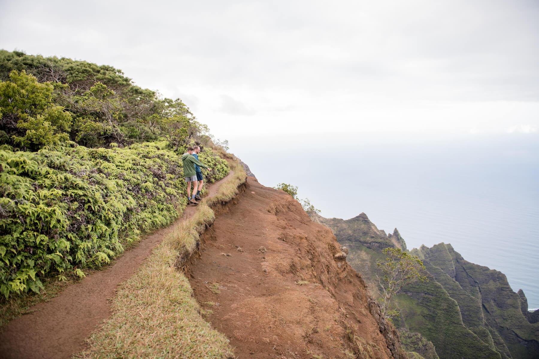 LGBTQ couple holding hands and hiking in Kauai, Hawaii